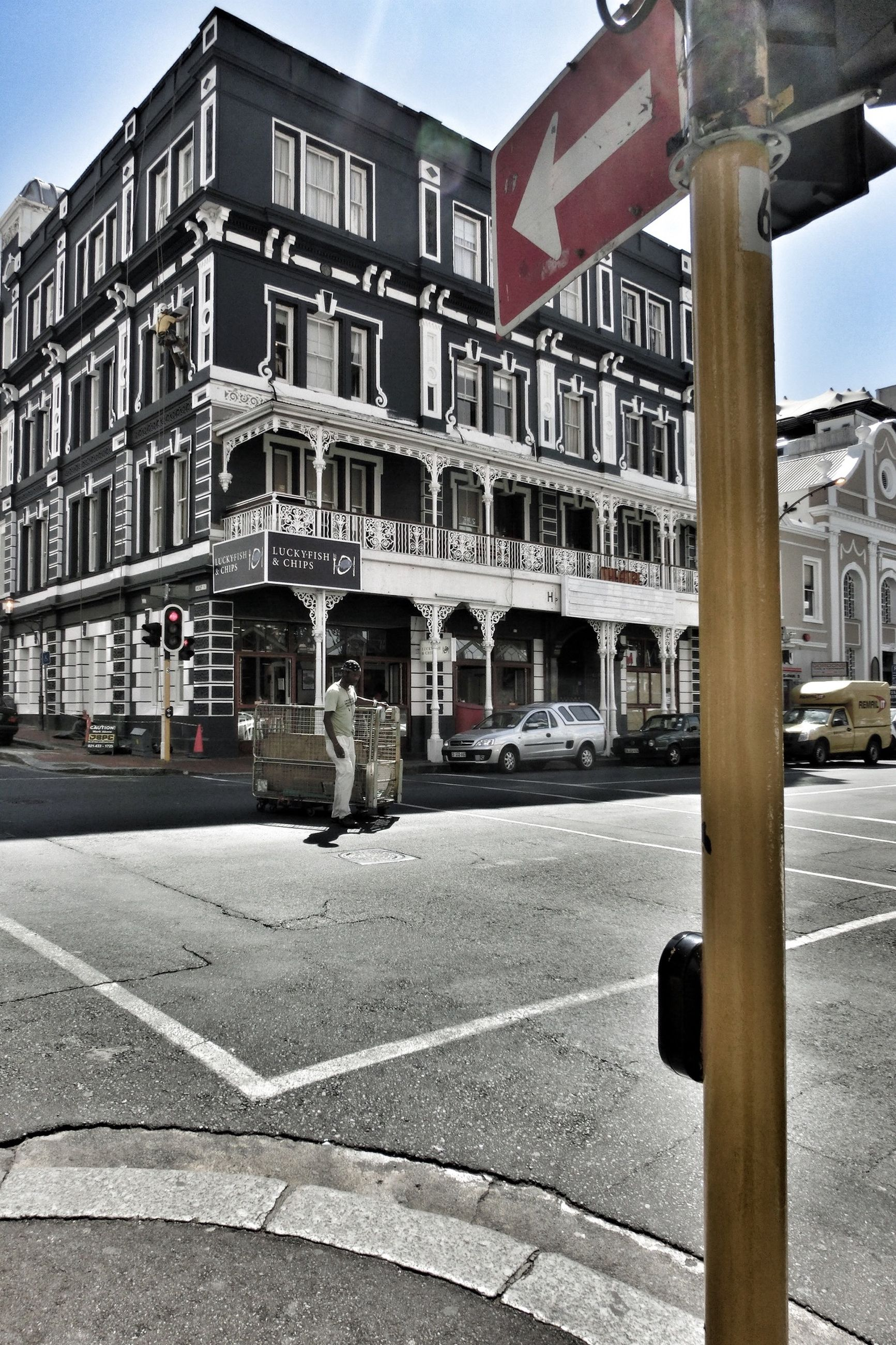 architecture, building exterior, built structure, city, street, transportation, road, car, sky, building, incidental people, arch, architectural column, city street, travel destinations, sunlight, clear sky, history, road marking, day