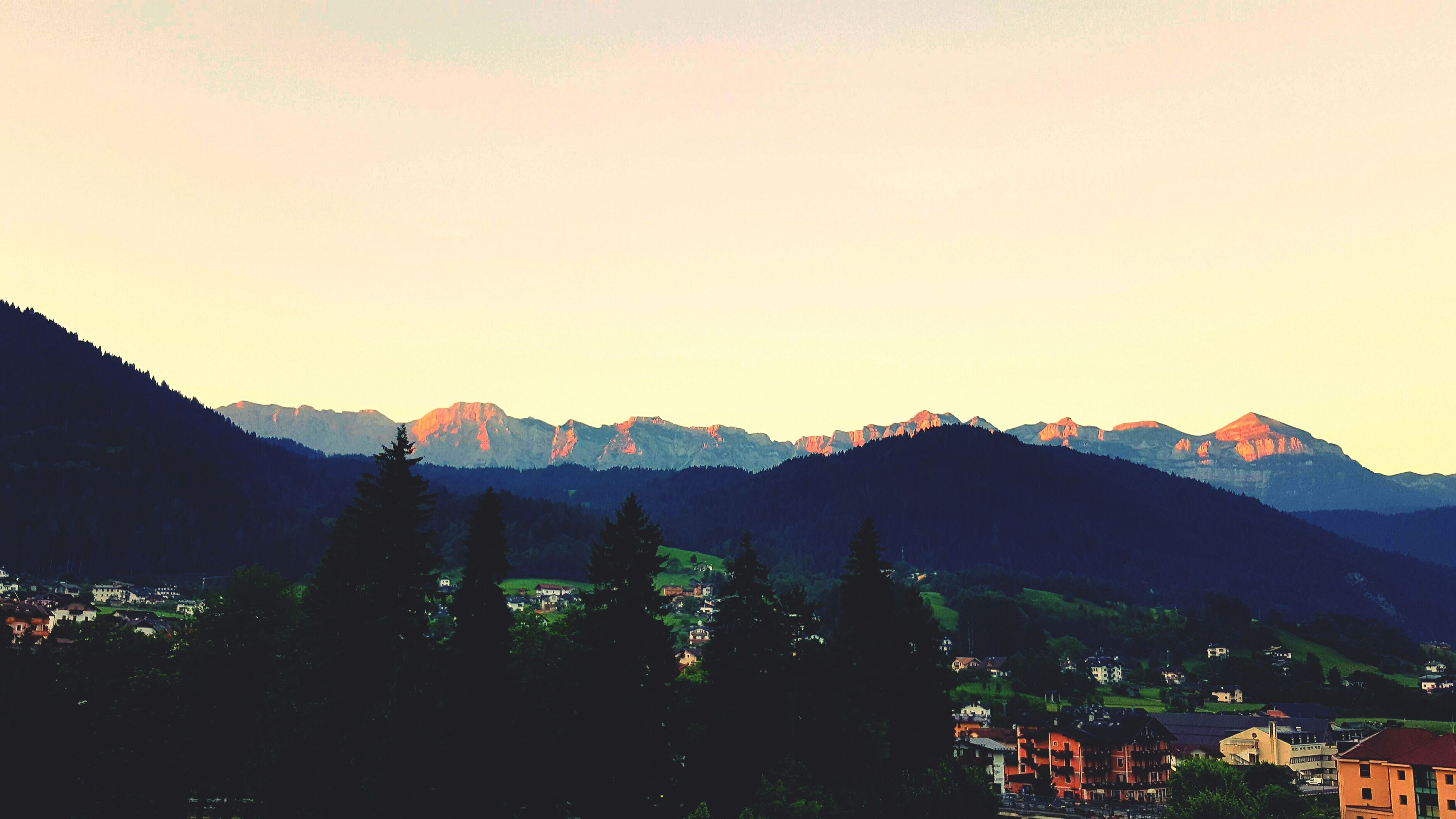 mountain, mountain range, clear sky, copy space, scenics, beauty in nature, tranquility, tranquil scene, silhouette, landscape, nature, building exterior, idyllic, outdoors, sunset, built structure, tree, no people, dusk, hill