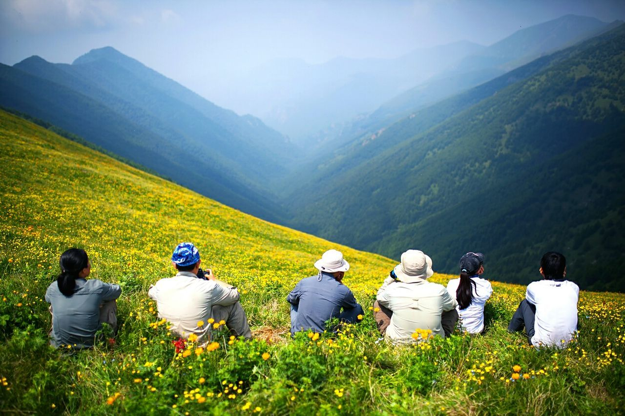 Rear View Of Friends Sitting On Grassy Field At Mountain