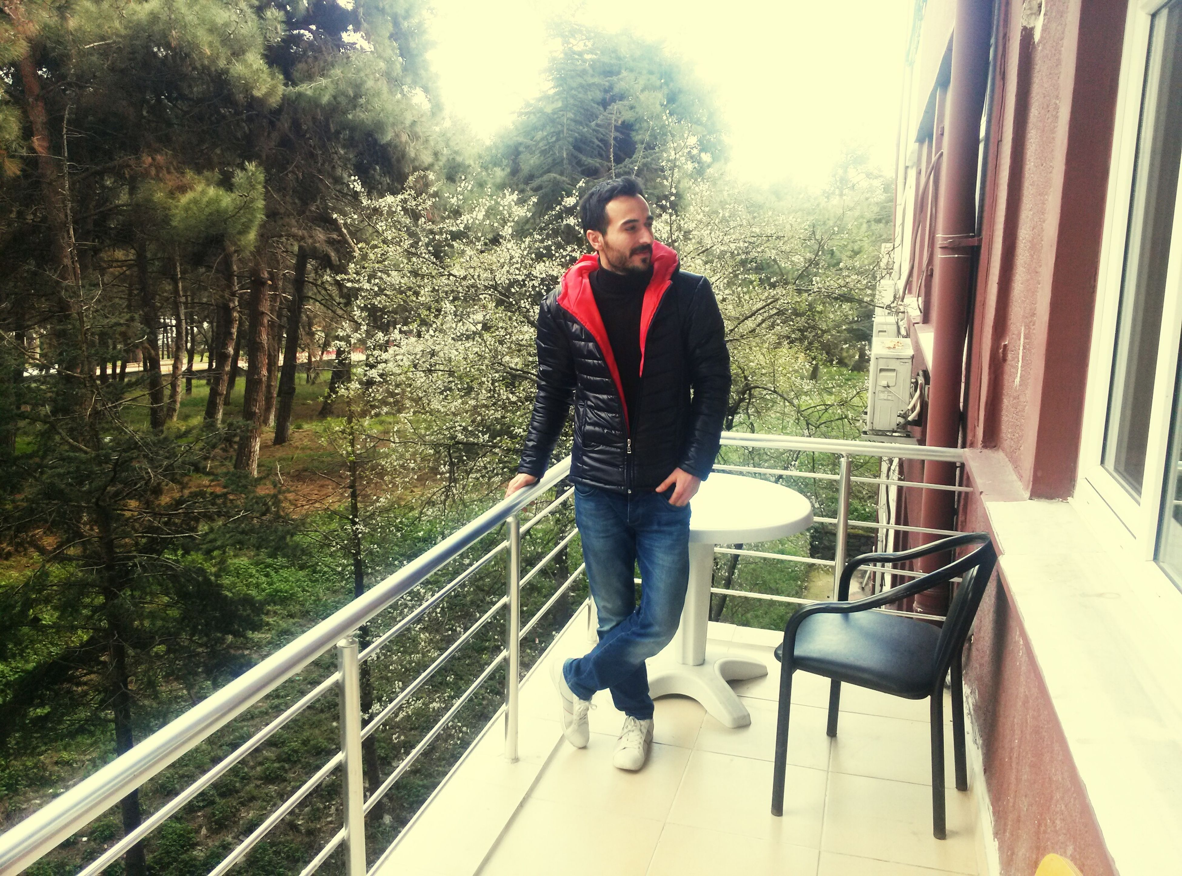 full length, casual clothing, lifestyles, person, railing, tree, leisure activity, built structure, architecture, young adult, standing, building exterior, young men, front view, sitting, steps, looking at camera, day