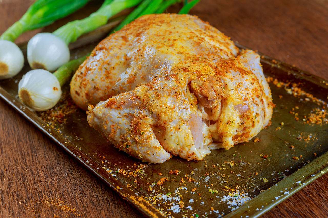 Close-Up Of Marinated Chicken Meat With Scallions On Table