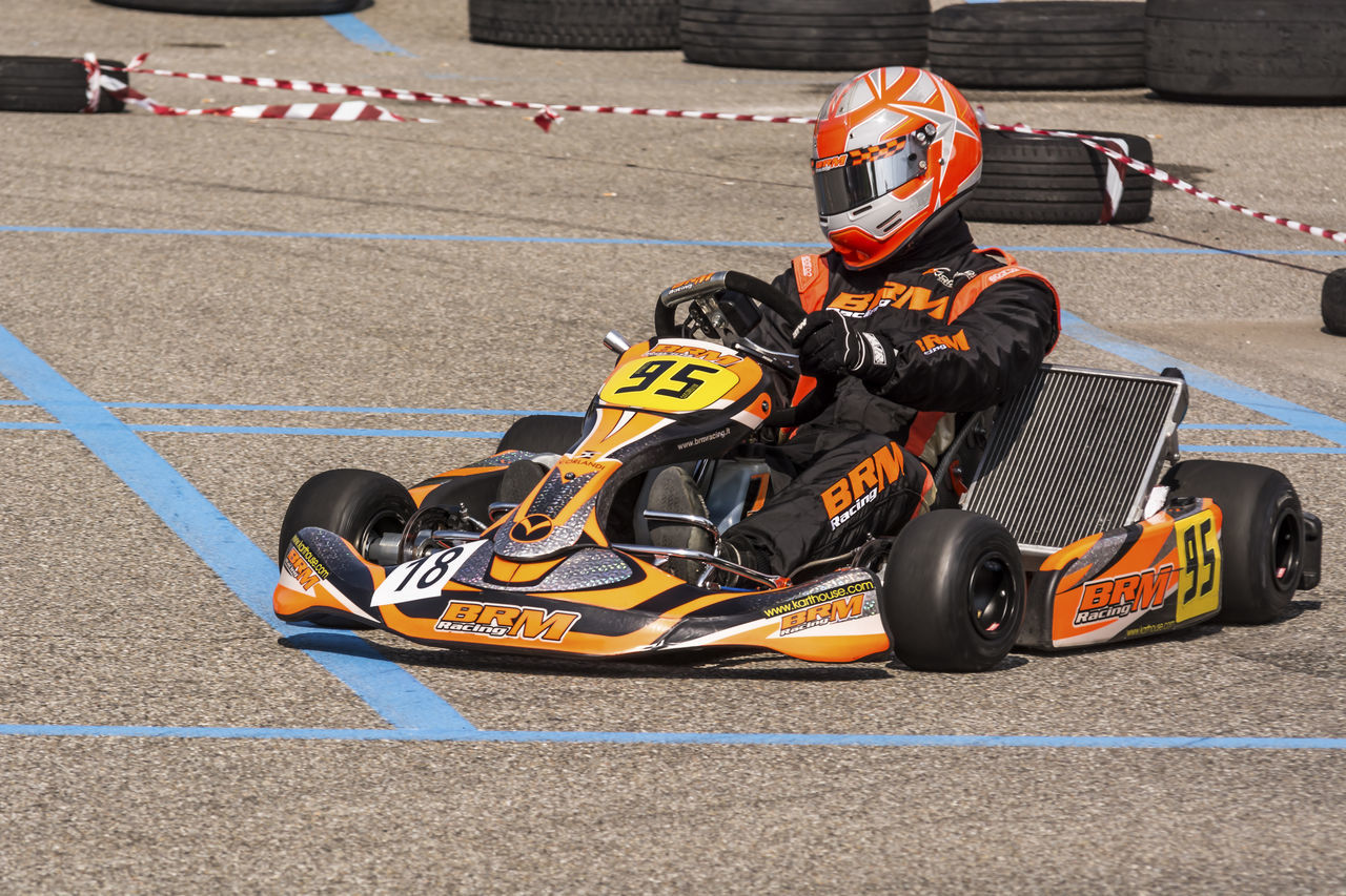 portrait of a go kart at a public event held in a parking lot Adults Only Auto Racing Beginnings Competition Competitive Sport Crash Helmet Day Formula One Racing Motion Motor Racing Track Motorsport Outdoors People Professional Sport Racecar Rivalry Speed Sport Sports Race Sports Track Starting Line Two People