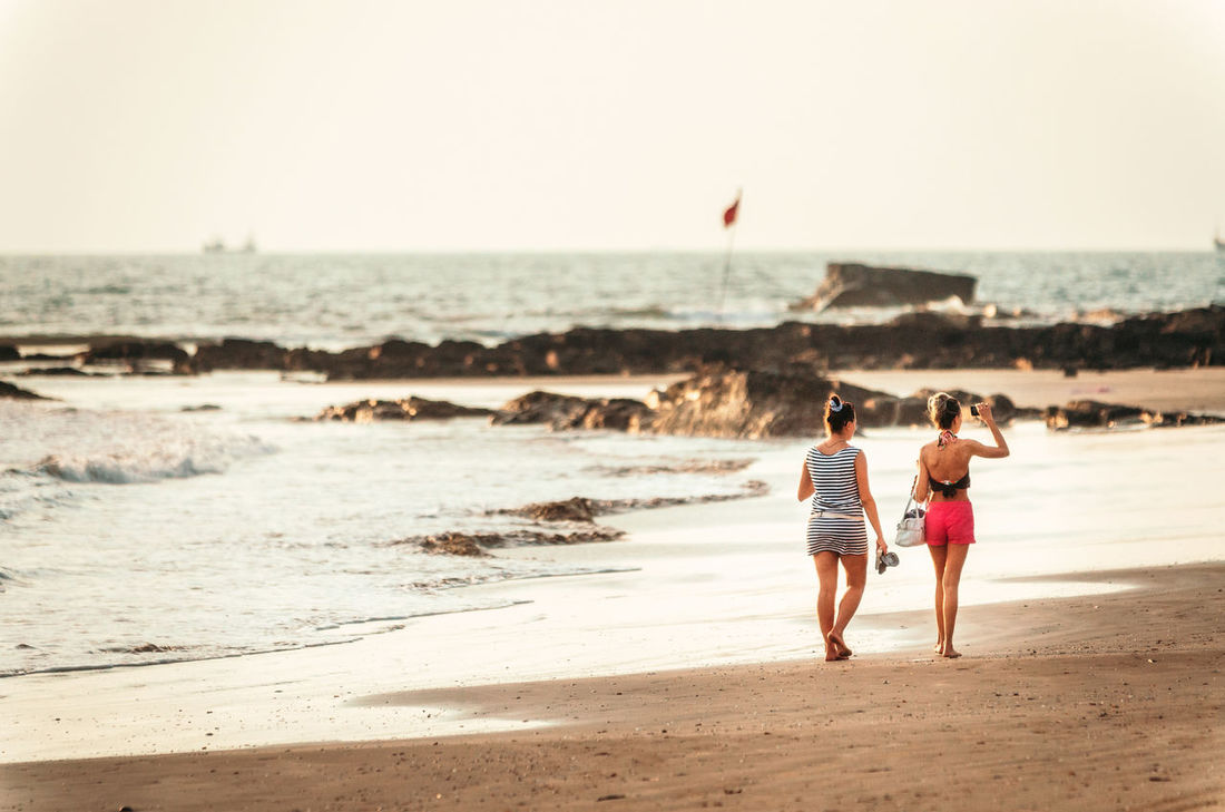 Two girls walk along the sandy beach at sunset in Goa Beach Casual Clothing Clear Sky Cliffs Girls Goa Horizon Over Water India Leisure Activity Lifestyles Morjim Nature Sand Sand & Sea Sea Shore Summertime Togetherness Vacations Water