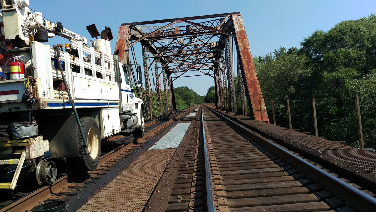 railroad track, transportation, rail transportation, bridge - man made structure, connection, day, metal, outdoors, the way forward, public transportation, built structure, no people, mode of transport, architecture, train - vehicle, tree, clear sky, sky