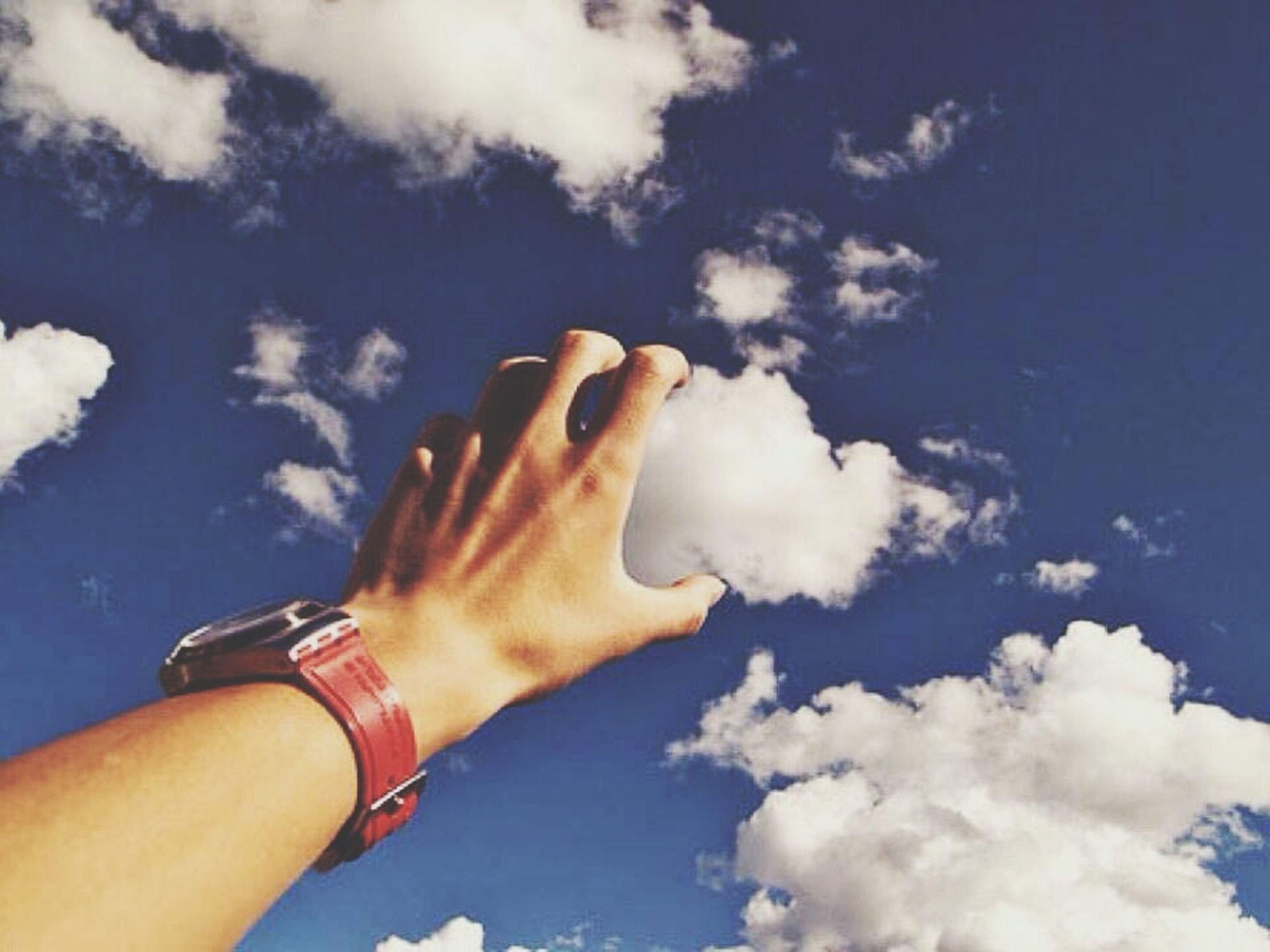 person, part of, holding, human finger, cropped, personal perspective, sky, cloud - sky, blue, unrecognizable person, low angle view, lifestyles, leisure activity, cloud, showing, day, close-up