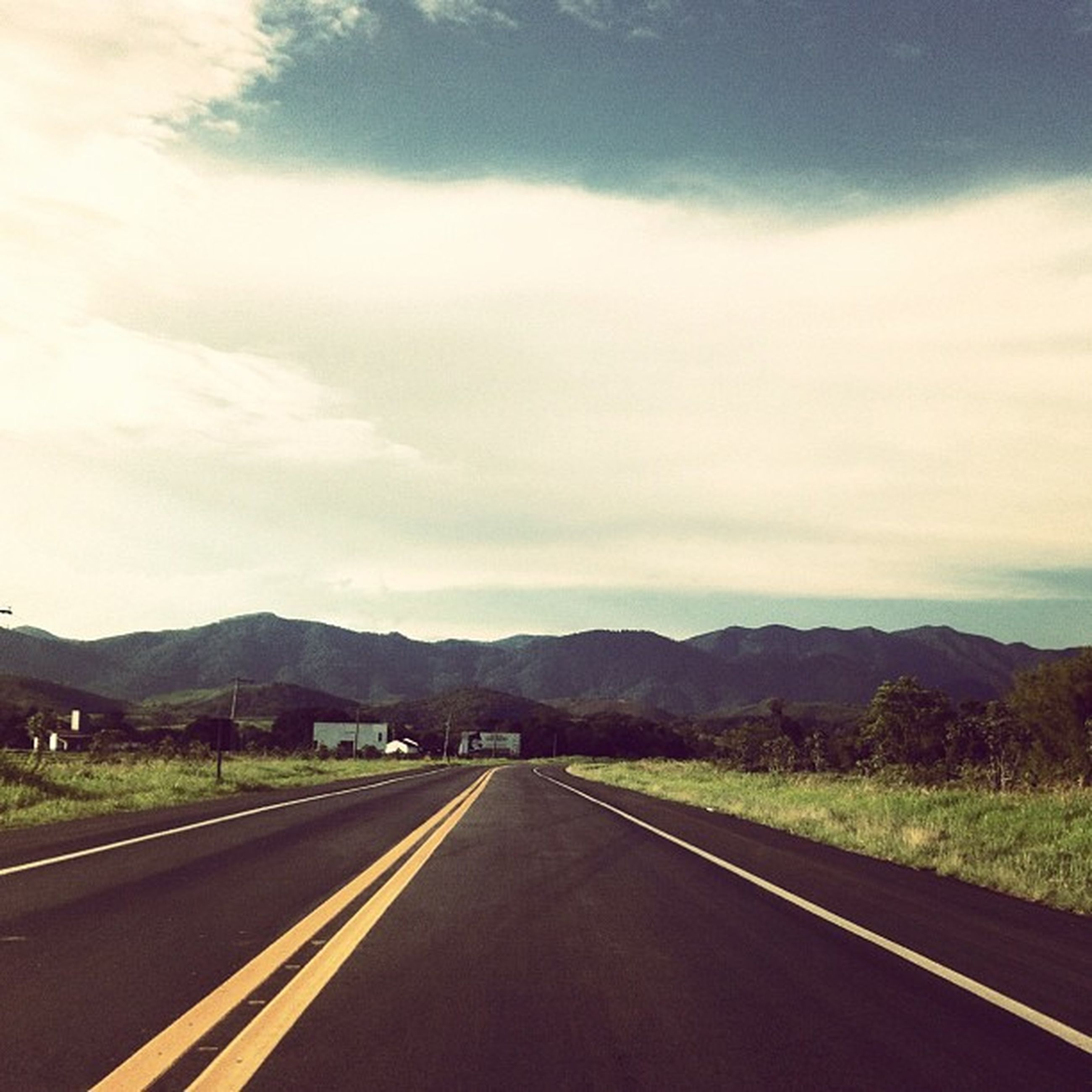 road, transportation, mountain, the way forward, sky, road marking, mountain range, country road, diminishing perspective, cloud - sky, landscape, vanishing point, cloud, highway, scenics, tranquil scene, empty, car, cloudy, nature