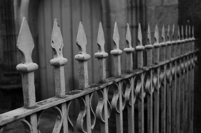 Balustrade Black & White Close-up Fence Focus On Foreground Full Frame Gate In A Row Industry Iron Iron - Metal Metal Metallic Monochrome Protection Railing Repetition Safety Selective Focus Separation Spiked Wrought Iron