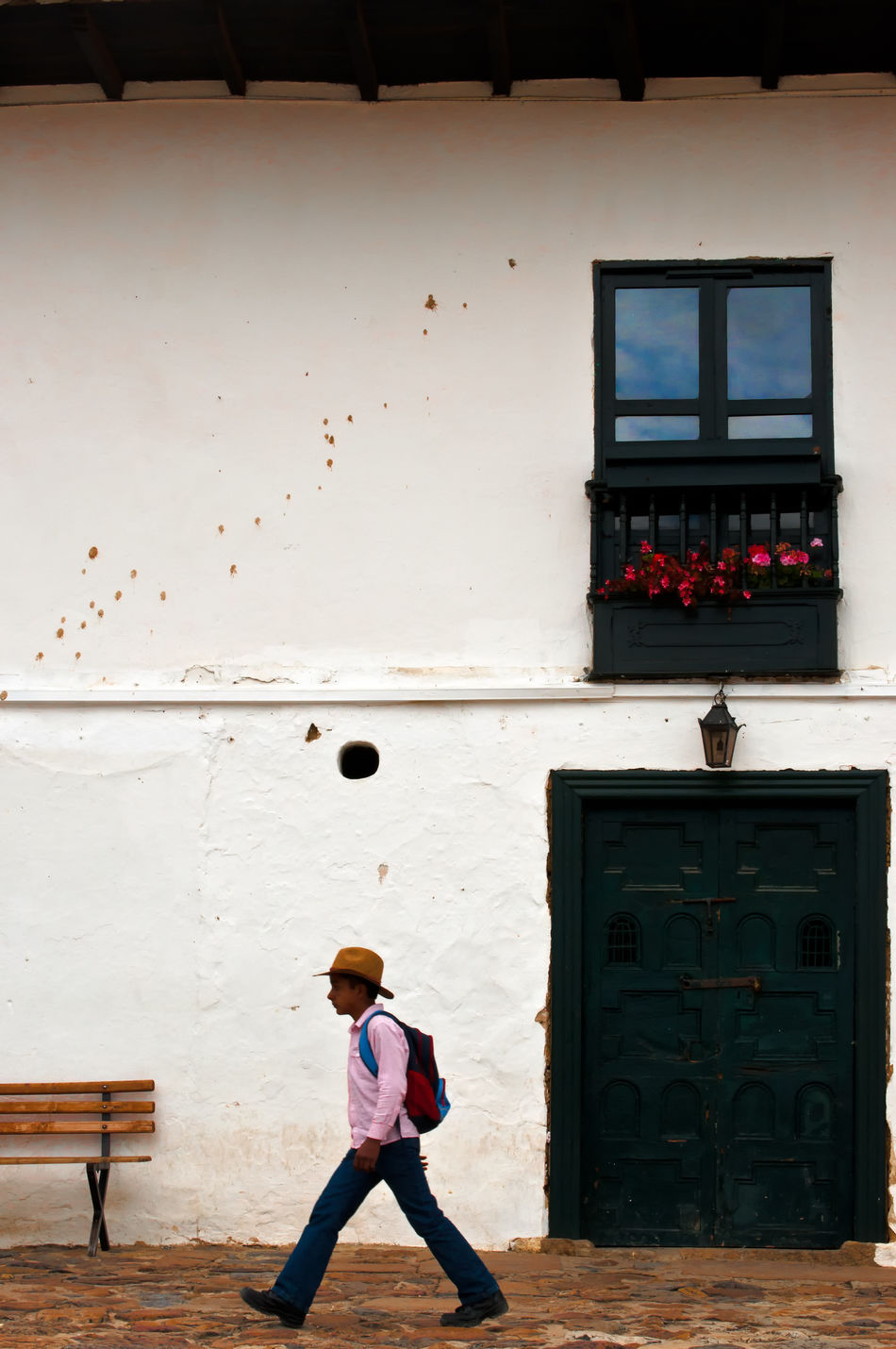 A young boy walking in front of an old colonial building. America Architecture Boyaca Building Colombia Colonial Country Countryside Exterior Historic House Latin Outdoors Residence South Stone Style Town Travel Typical VillaDeLeyva Wall White Window Wood