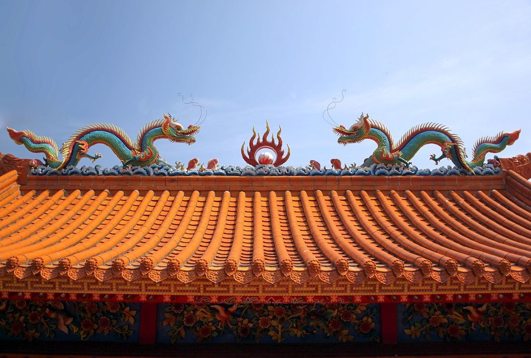 Two elaborate dragons decorate a Chinese temple roof Architecture Ceramics Chinese Architecture Chinese Temple Decoration Dragon Sculpture Eaves Glazed Tile Mythology Pottery Symmetry Temple Roof