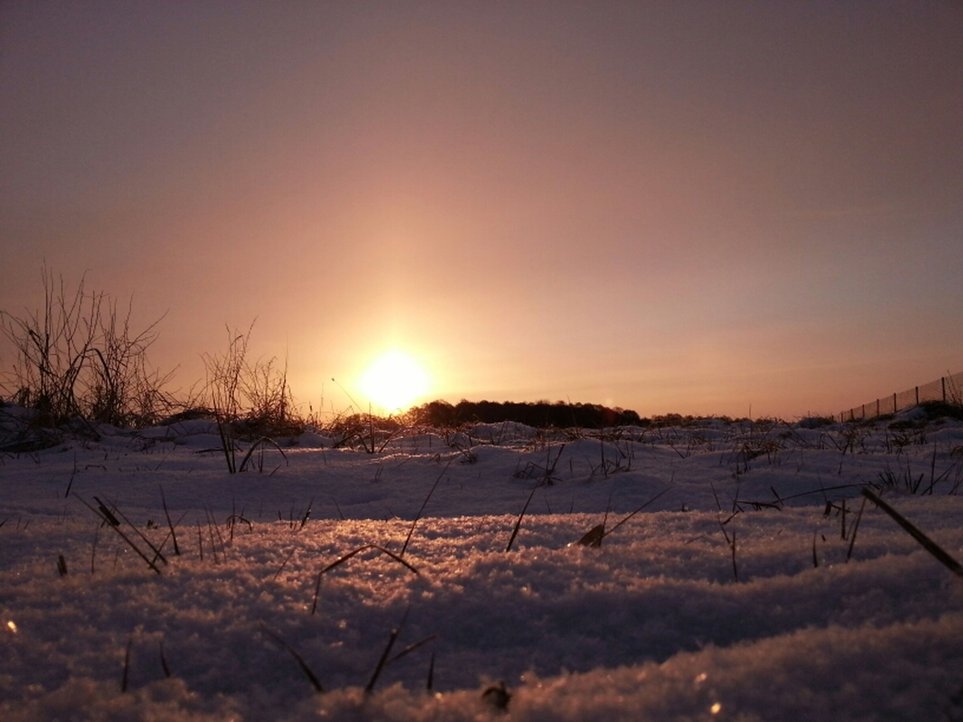 winter, snow, cold temperature, sunset, sun, season, landscape, tranquil scene, tranquility, field, weather, covering, scenics, beauty in nature, orange color, nature, clear sky, frozen, sunlight, sky
