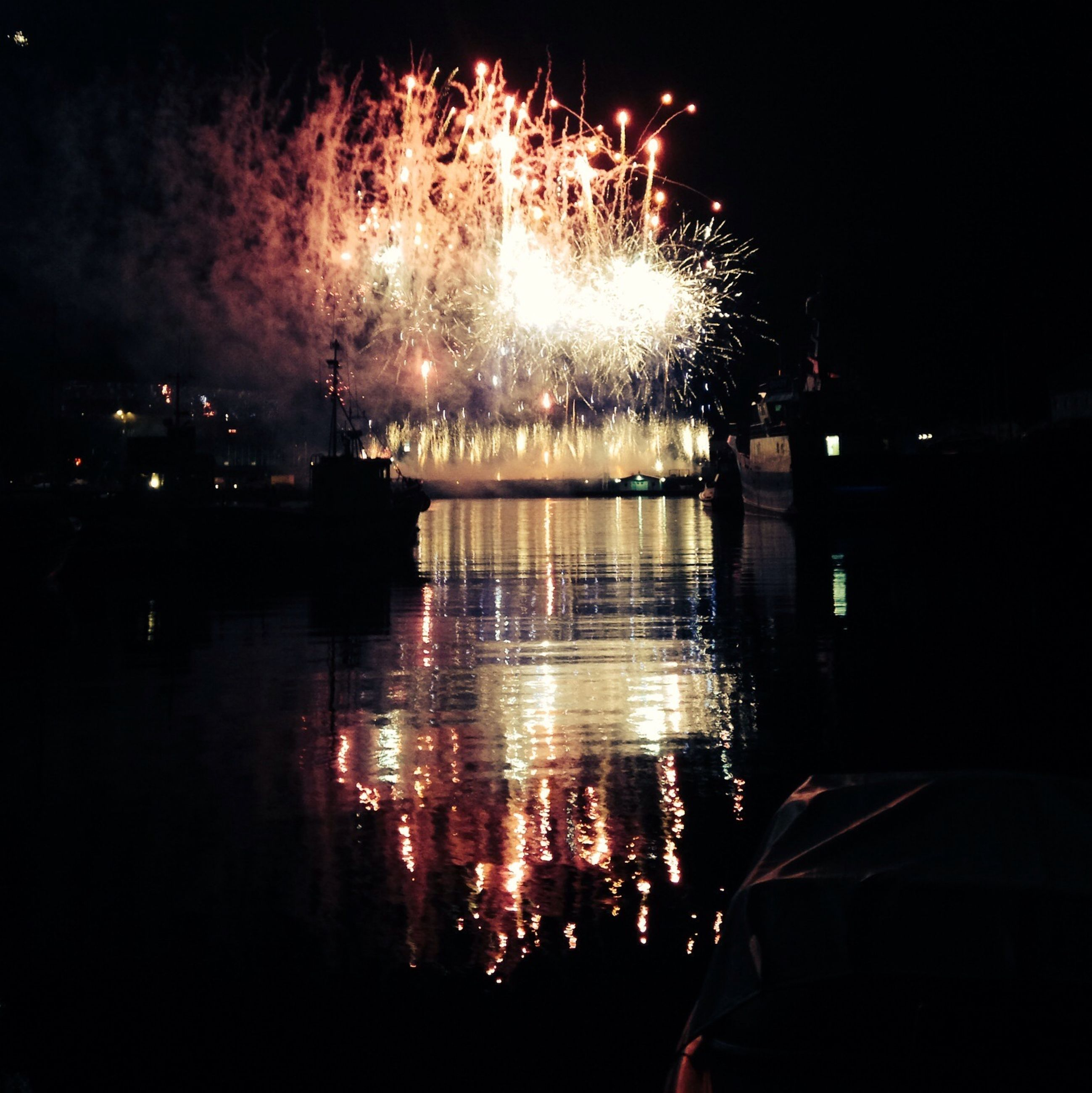 night, illuminated, firework display, long exposure, glowing, water, exploding, celebration, sparks, building exterior, reflection, firework - man made object, sky, motion, city, river, event, arts culture and entertainment, firework, entertainment