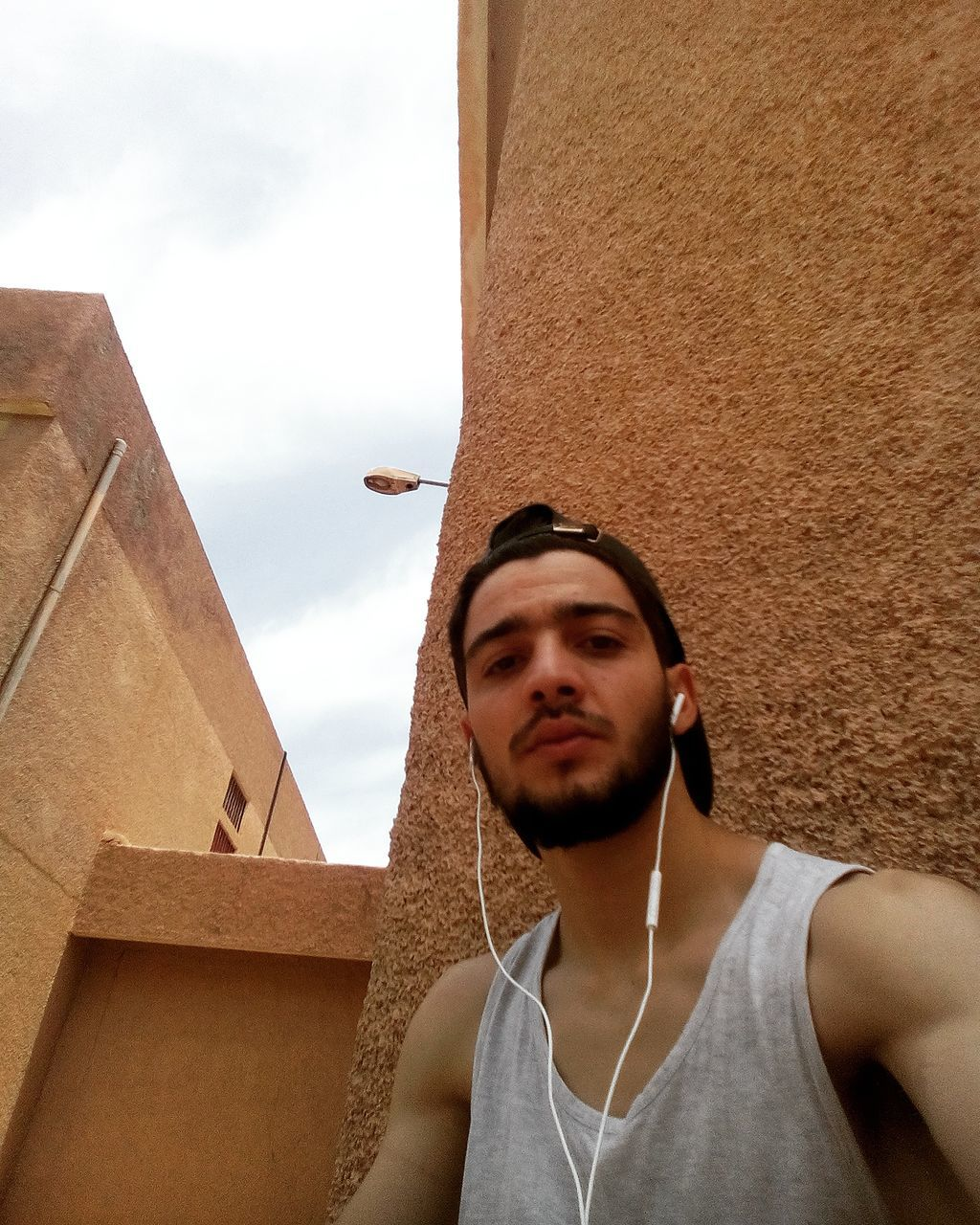 young adult, one person, young men, real people, leisure activity, lifestyles, day, listening, built structure, casual clothing, outdoors, standing, one young man only, architecture, low angle view, music, men, sky, young women, building exterior, one man only, people