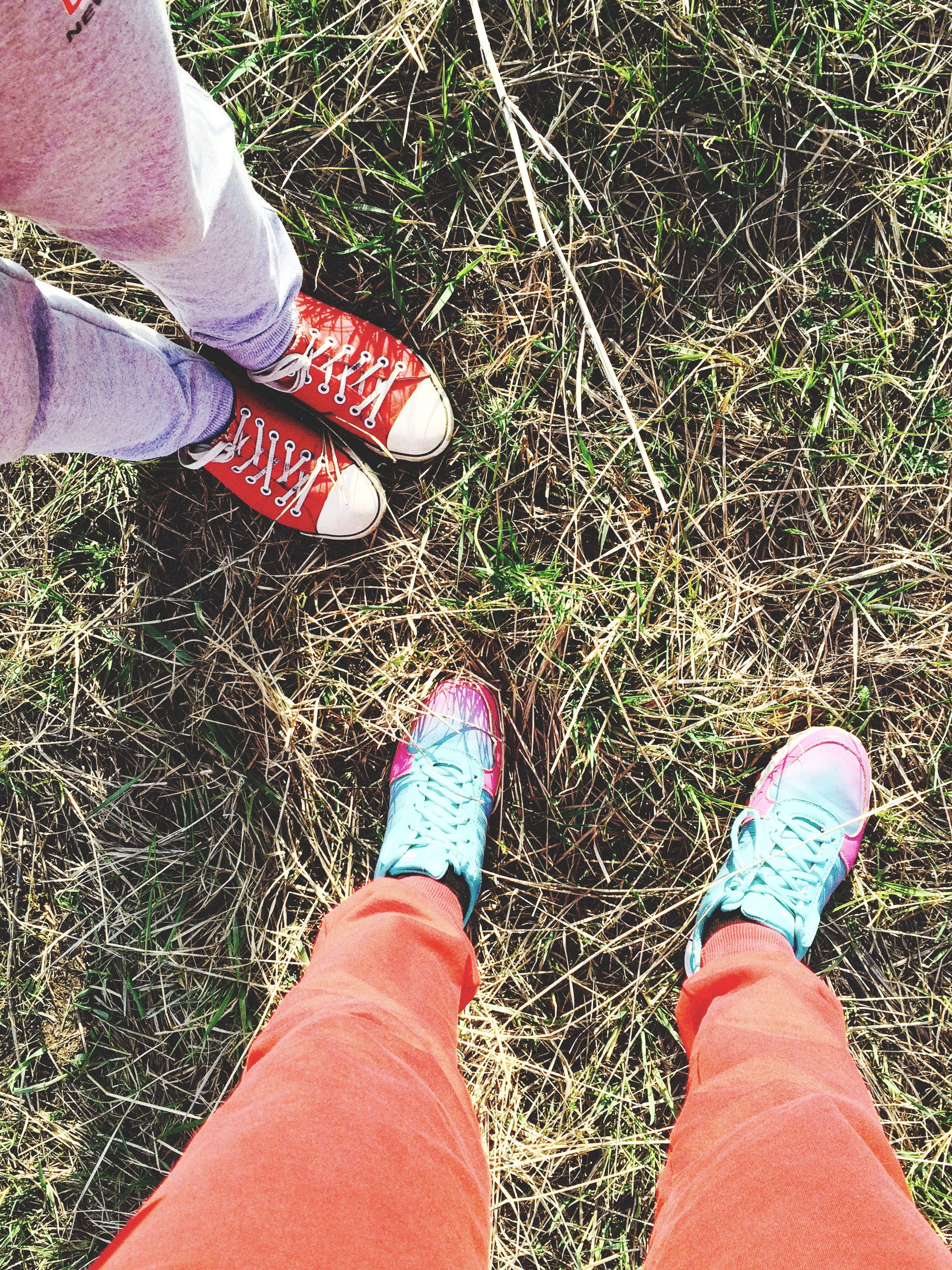 low section, person, shoe, personal perspective, human foot, footwear, lifestyles, high angle view, standing, leisure activity, grass, jeans, part of, directly above, canvas shoe, unrecognizable person