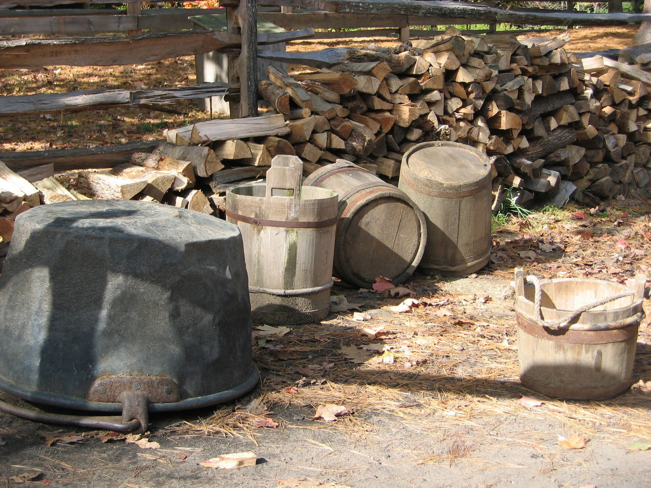 Buckets Cauldron Farm Fence Firewood Heap Log Man Made Object No People Outdoors Rocky Split Rail Fence Stone Material Stone Wall Wood Barrels Wood Pile