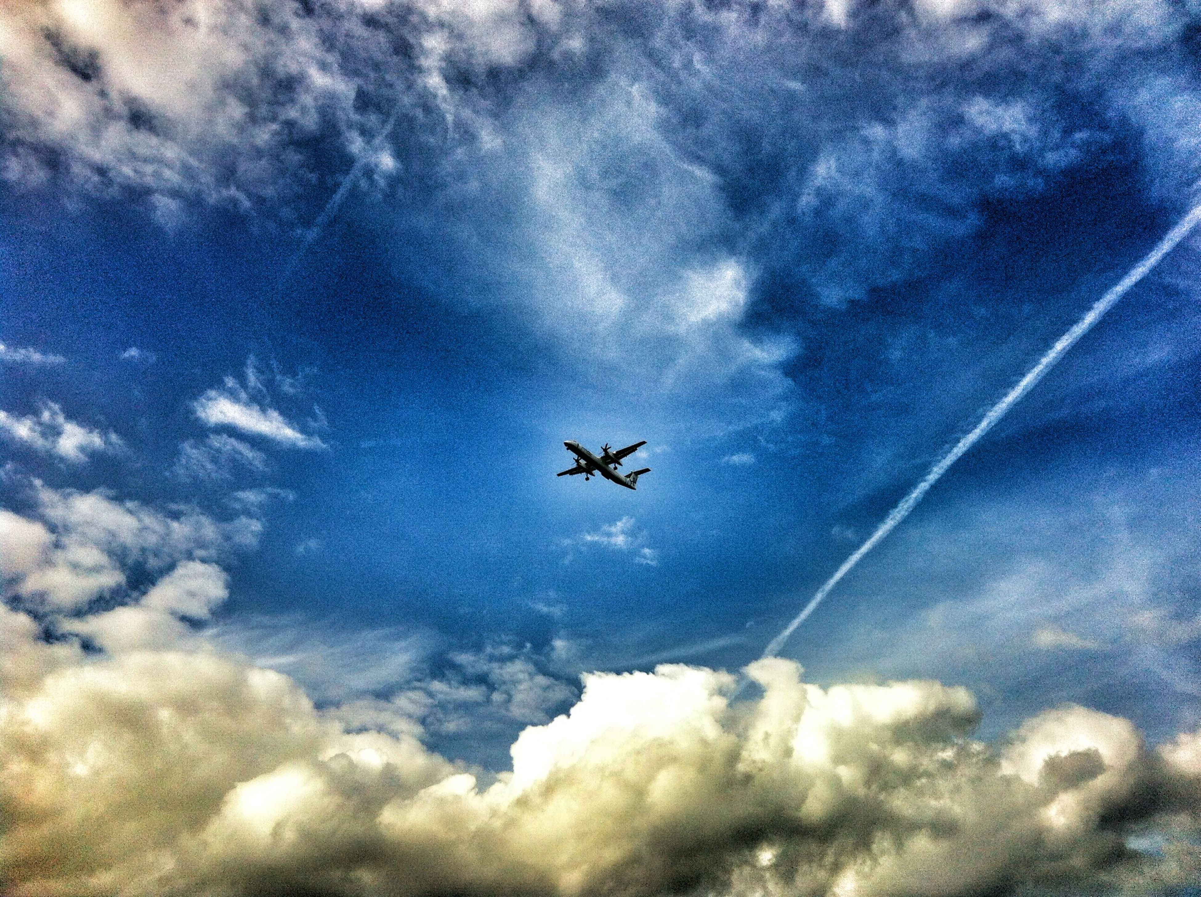 transportation, airplane, air vehicle, mode of transport, flying, sky, cloud - sky, mid-air, low angle view, on the move, public transportation, cloudy, travel, journey, cloud, aircraft wing, cloudscape, commercial airplane, nature, aircraft