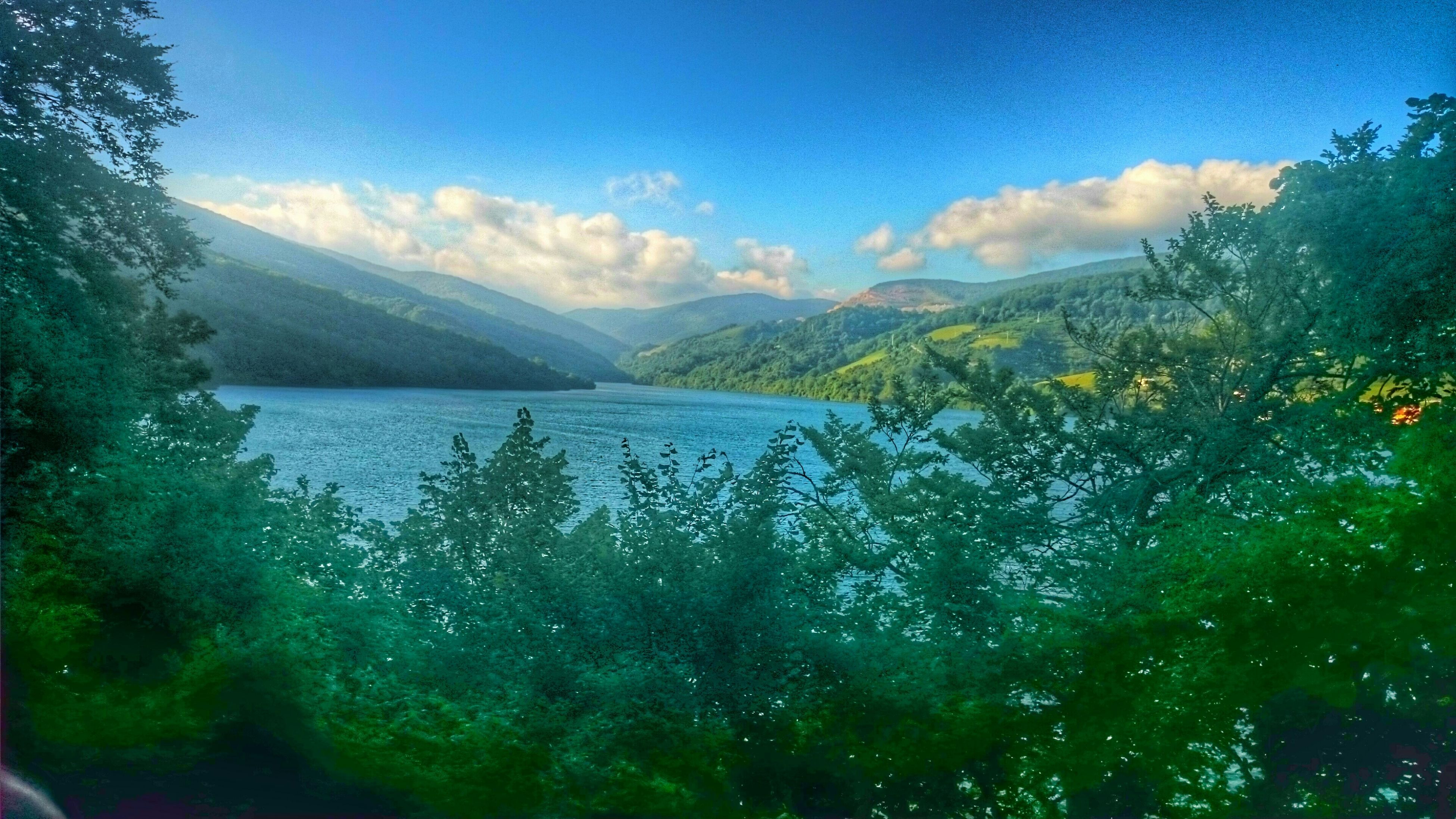 mountain, tranquil scene, tranquility, scenics, beauty in nature, water, mountain range, sky, lake, nature, tree, idyllic, landscape, blue, non-urban scene, cloud - sky, river, cloud, remote, day