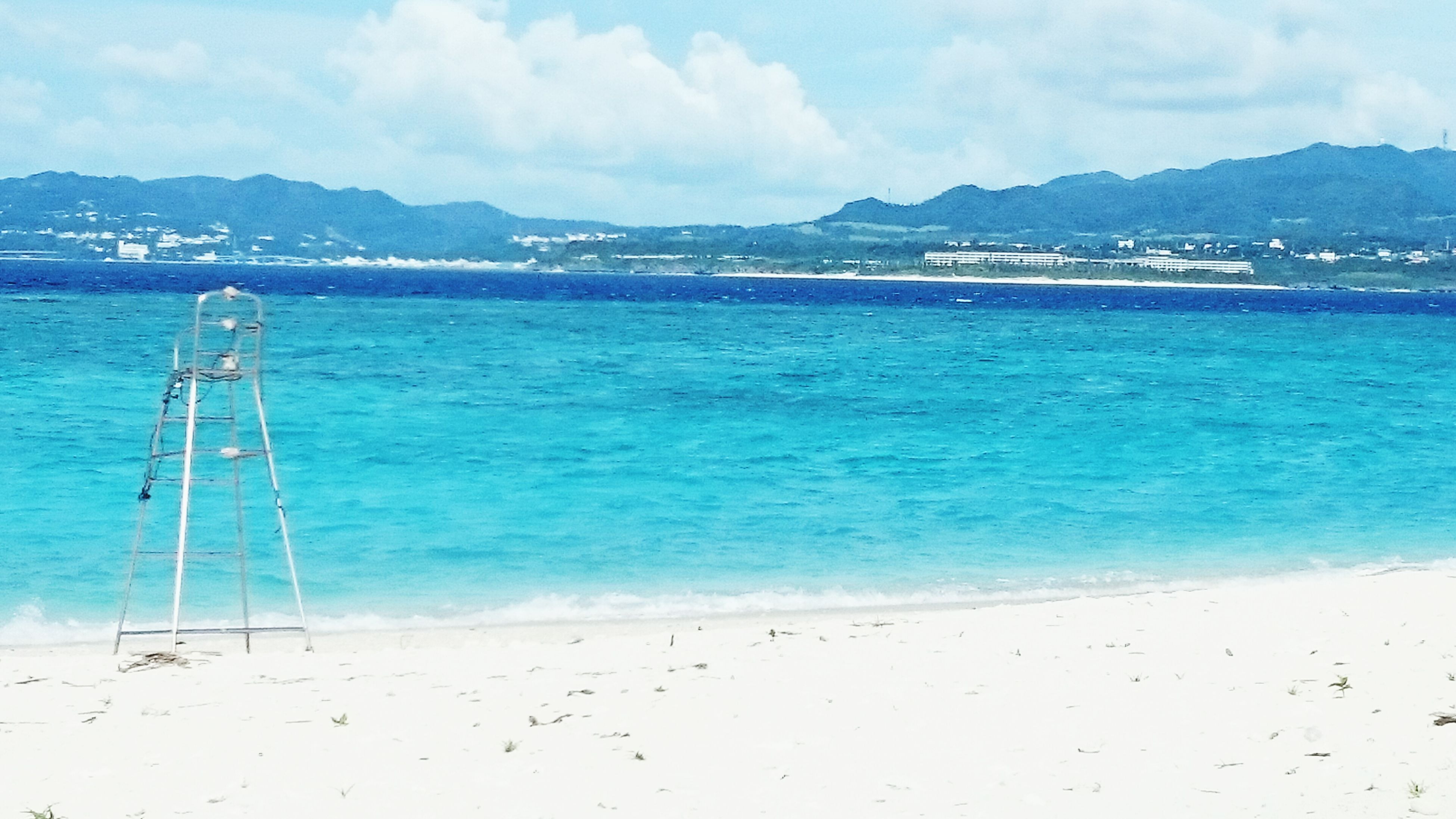 water, beach, blue, sea, mountain, scenics, tranquil scene, shore, sand, sky, tranquility, cloud - sky, mountain range, nature, beauty in nature, calm, day, outdoors, non-urban scene, no people, remote, seascape, tourism, coastline, ocean, vacations, solitude