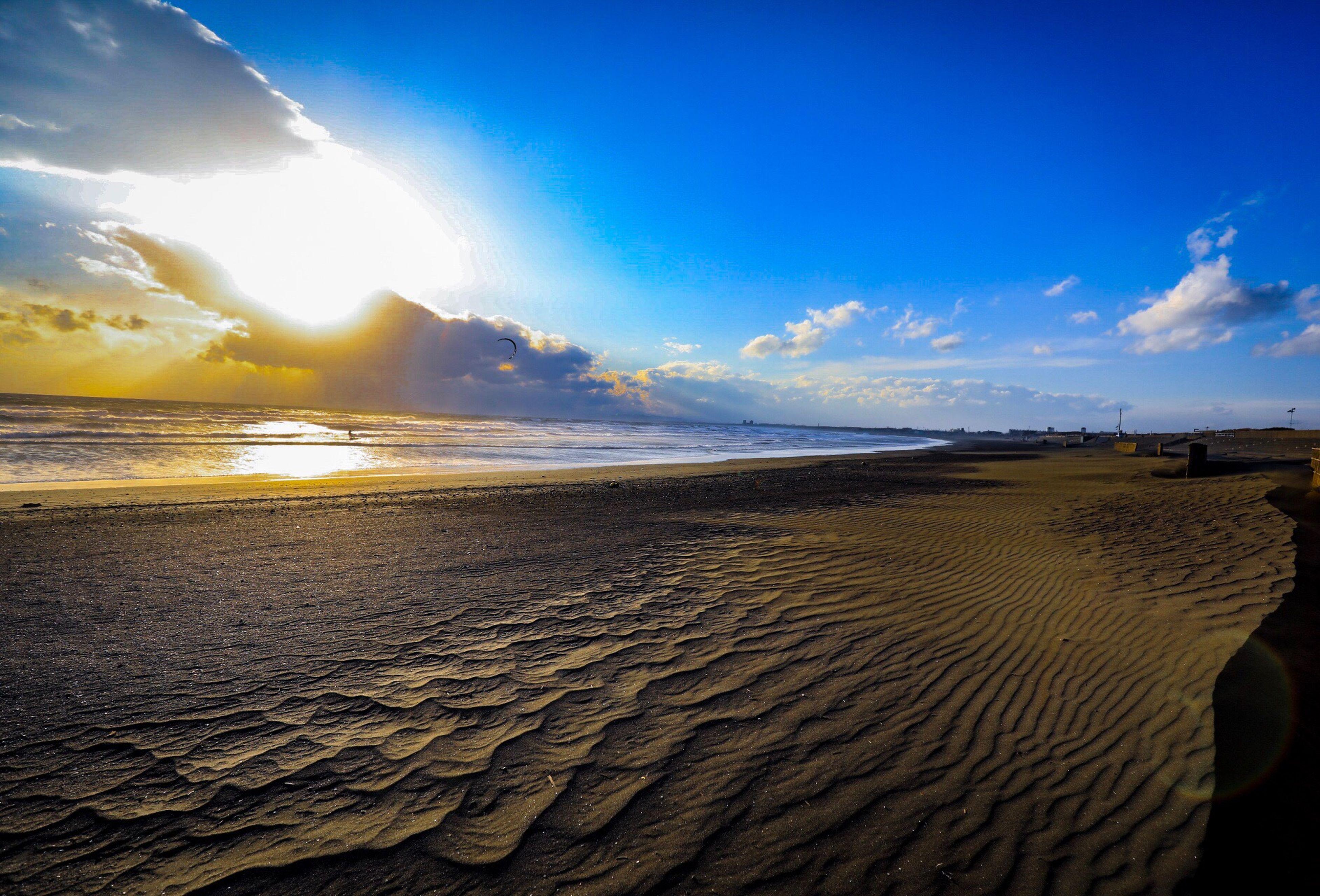 sand, sky, sunlight, nature, beach, sea, scenics, beauty in nature, outdoors, sun, sunbeam, sunset, tranquil scene, horizon over water, no people, day, water, sand dune