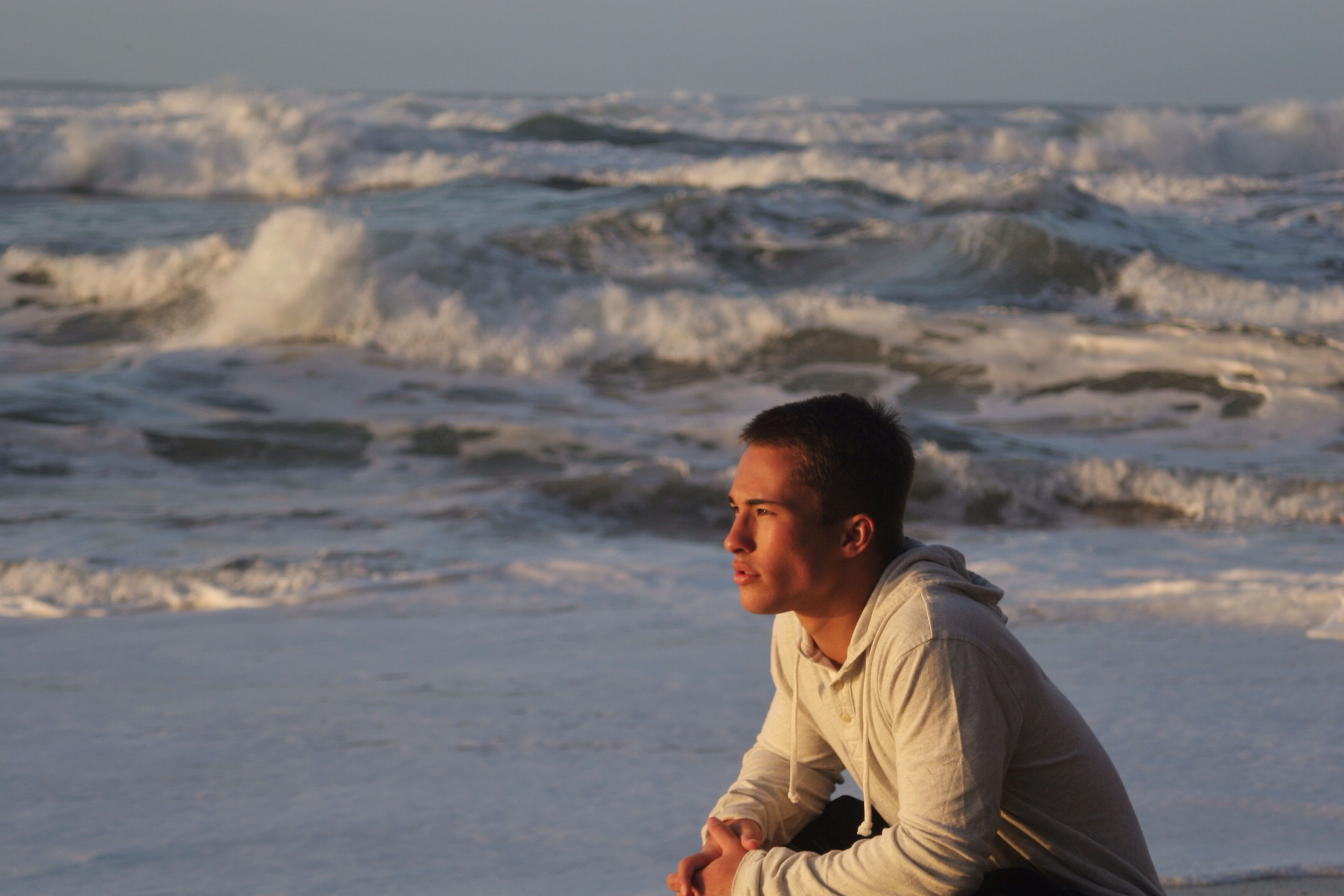 person, lifestyles, young adult, leisure activity, casual clothing, young men, water, headshot, focus on foreground, portrait, waist up, looking at camera, sea, smiling, standing, front view, beach