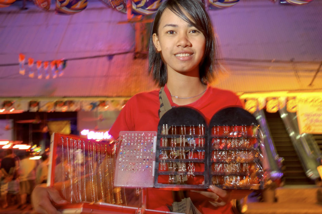 Thailand, Pattaya, Walking Street, Young girl selling custom jewelry Color Image Custom Jewelry Flash Photography Girl Horizontal Pattaya Selling Smiling Thailand Vendor Walking Street Pattaya Young Woman
