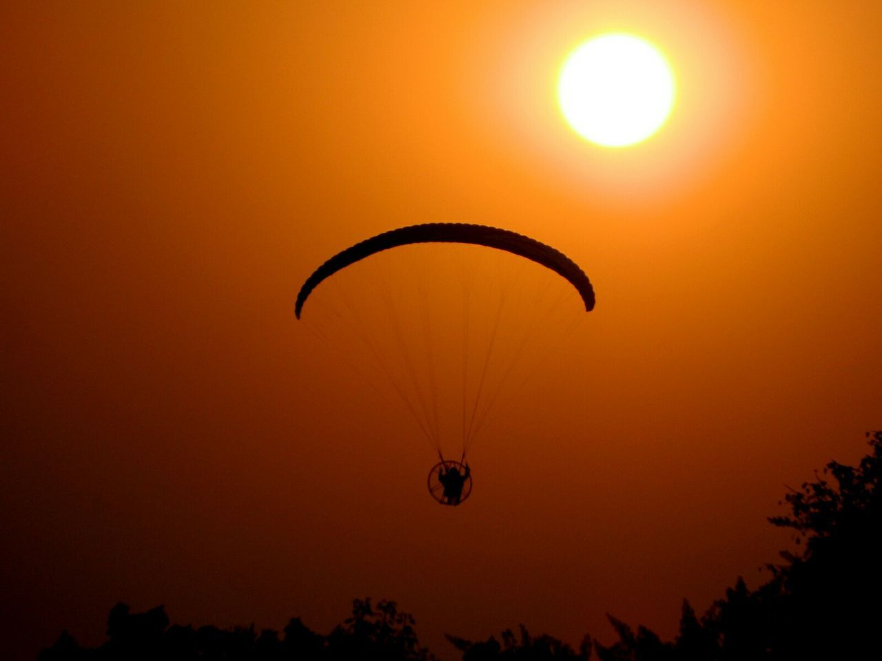 Low Angle View Of Silhouette Parachute Flying Against Orange Sky During Sunset