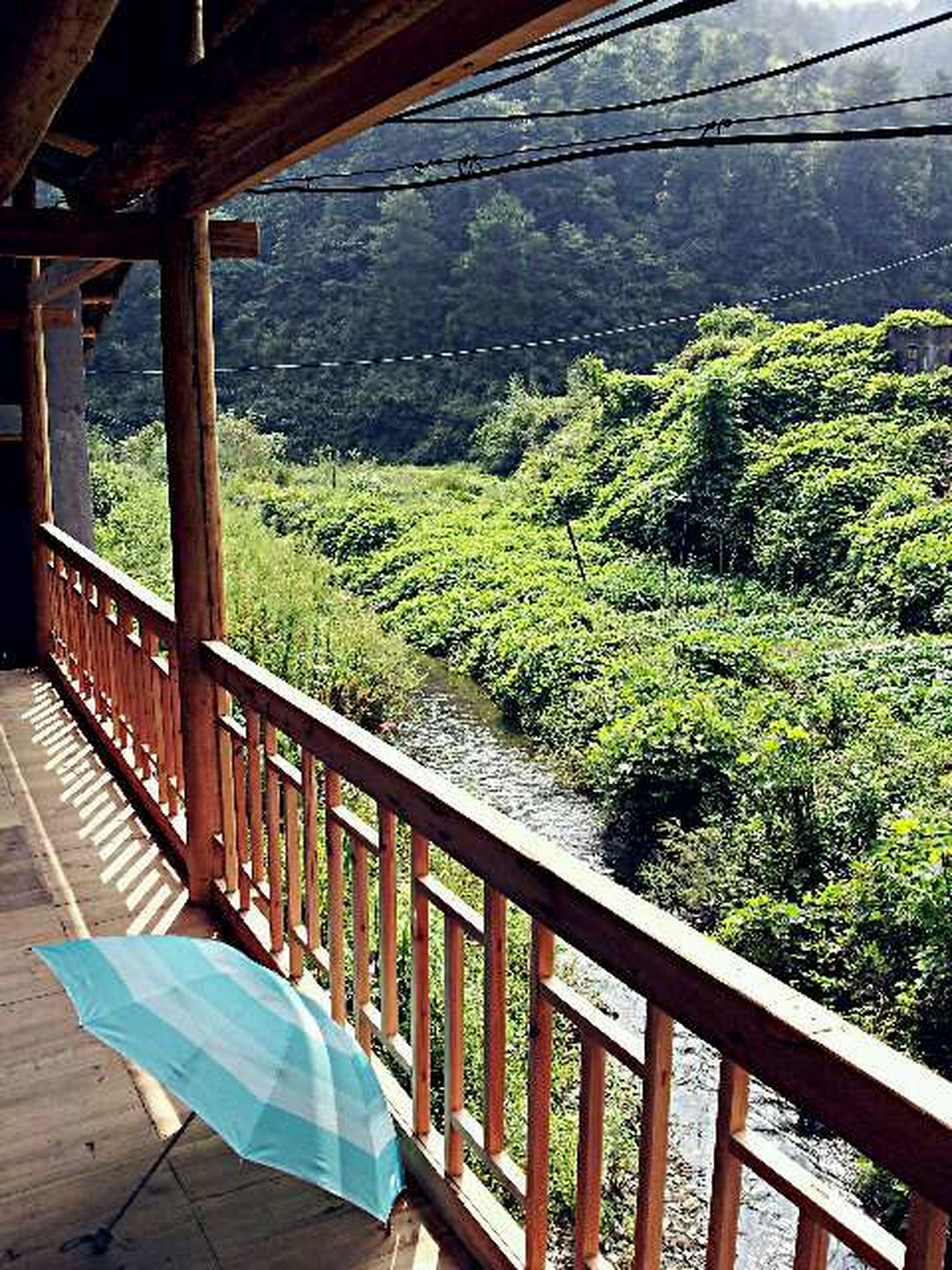 railing, water, tranquility, green color, nature, tranquil scene, tree, beauty in nature, connection, mountain, growth, scenics, high angle view, plant, day, sky, no people, built structure, bridge, bridge - man made structure