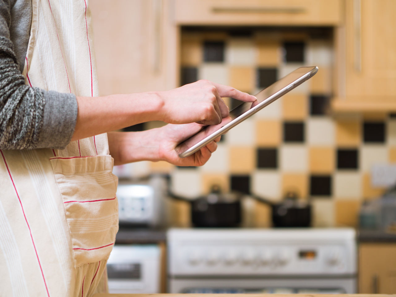 man using tablet in the kitchen Adult Adults Only Apron Close-up Communication Connection Day Digital Tablet Focus On Foreground Holding Human Body Part Human Hand Indoors  Kitchen Lifestyles Man Midsection One Person People Portable Information Device Real People Technology Wireless Technology