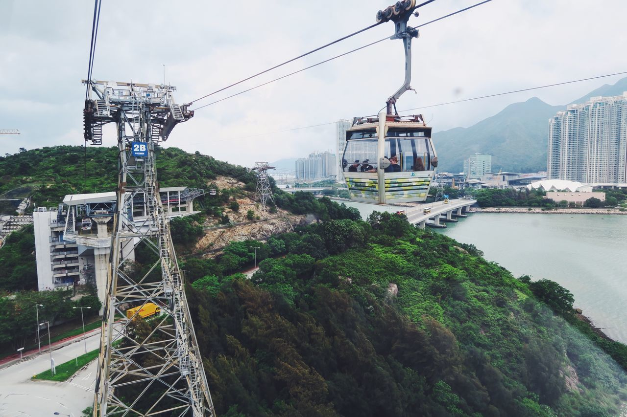 transportation, cable, mode of transport, connection, architecture, overhead cable car, built structure, mountain, day, sky, bridge - man made structure, outdoors, no people, building exterior, nature, water, electricity pylon, nautical vessel, tree, city