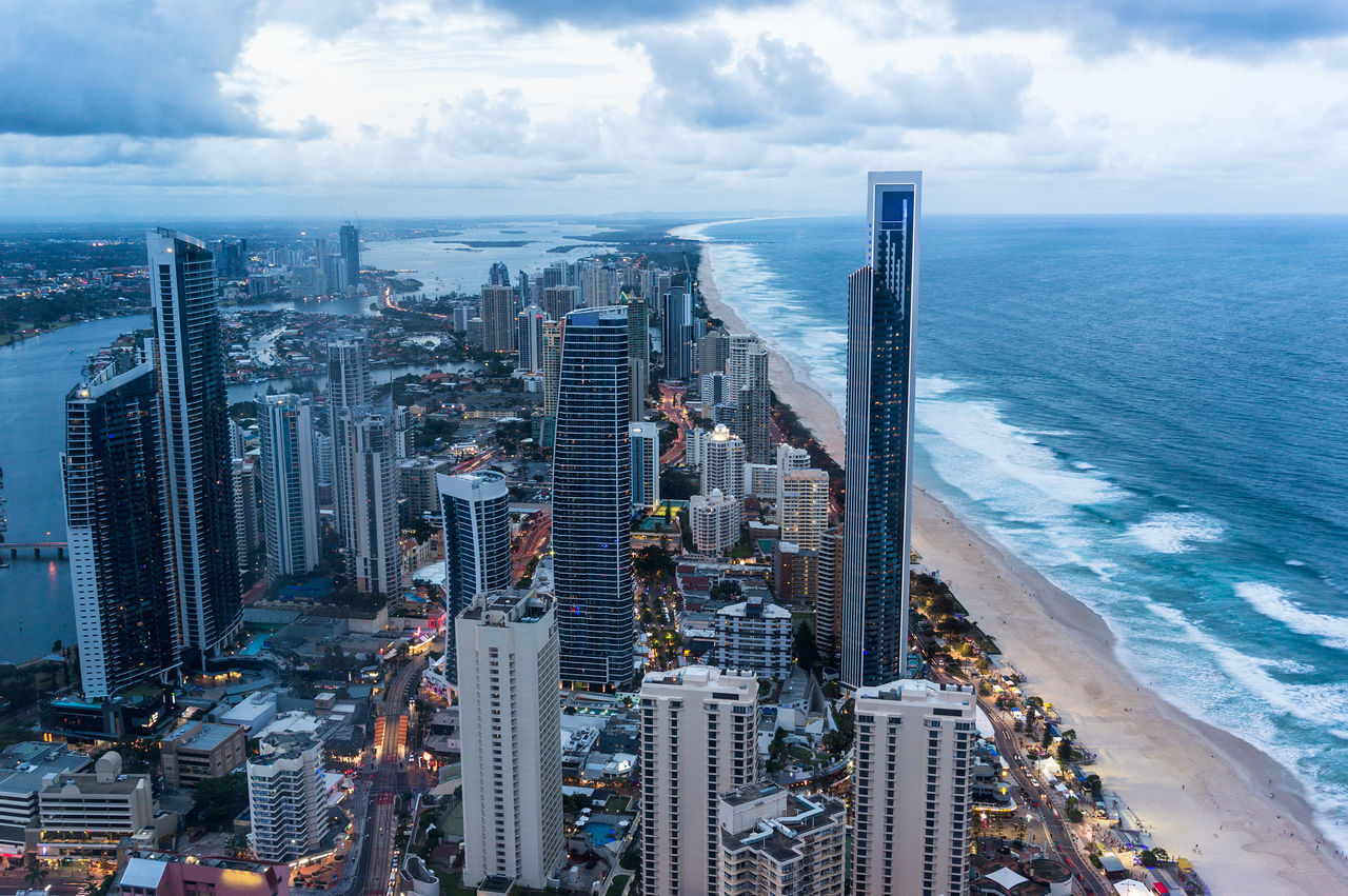 Aerial, view from above of modern city by the beach at dusk. Surfers Paradise town, Gold Coast, Queensland, Australia at dusk, aerial view Aerial View Australia Beach City Coastline Futuristic Gold Coast Modern Architecture Ocean Sea Surfers Paradise Urban View From Above