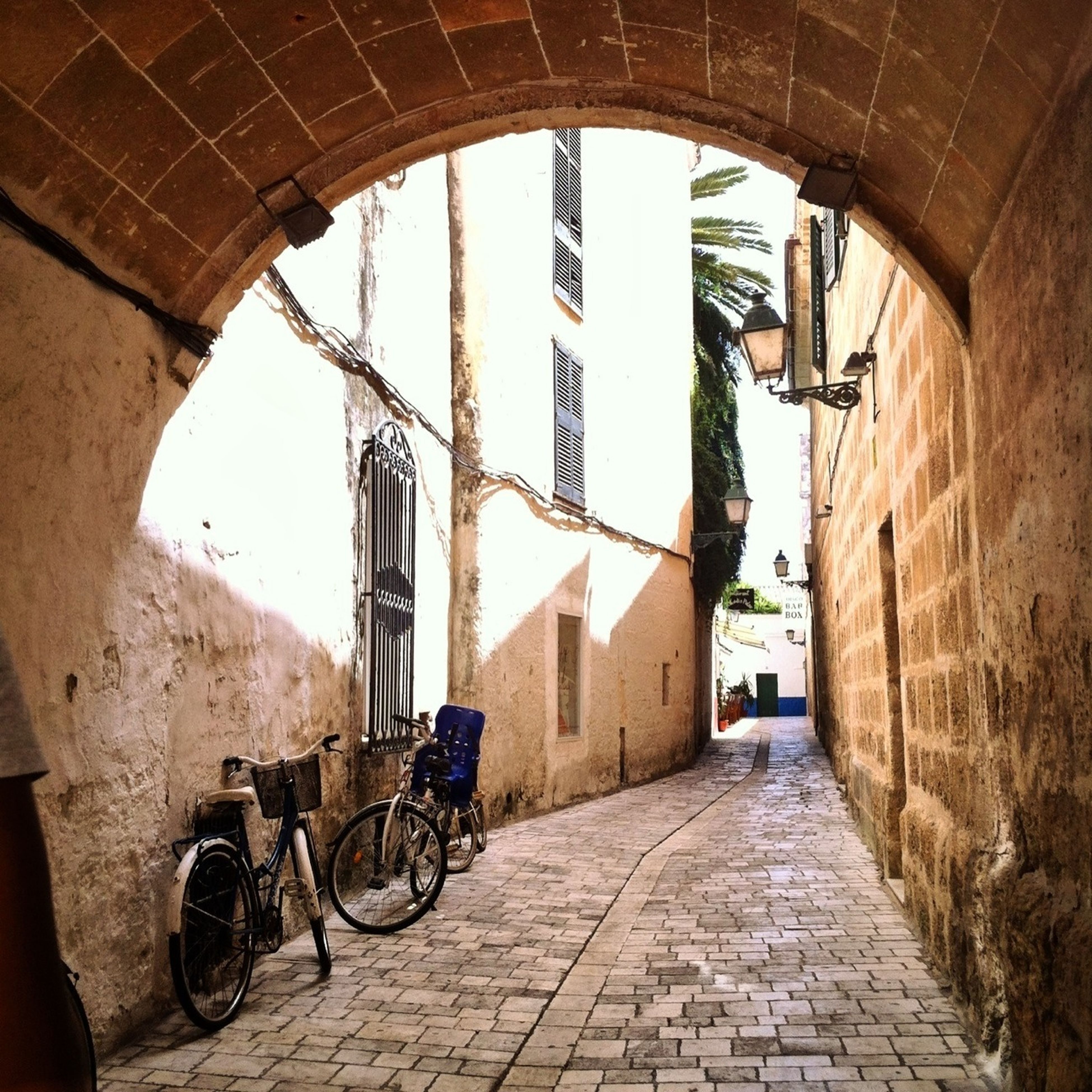 architecture, built structure, building exterior, the way forward, arch, bicycle, cobblestone, alley, street, building, diminishing perspective, narrow, footpath, archway, day, residential building, city, wall - building feature, old town