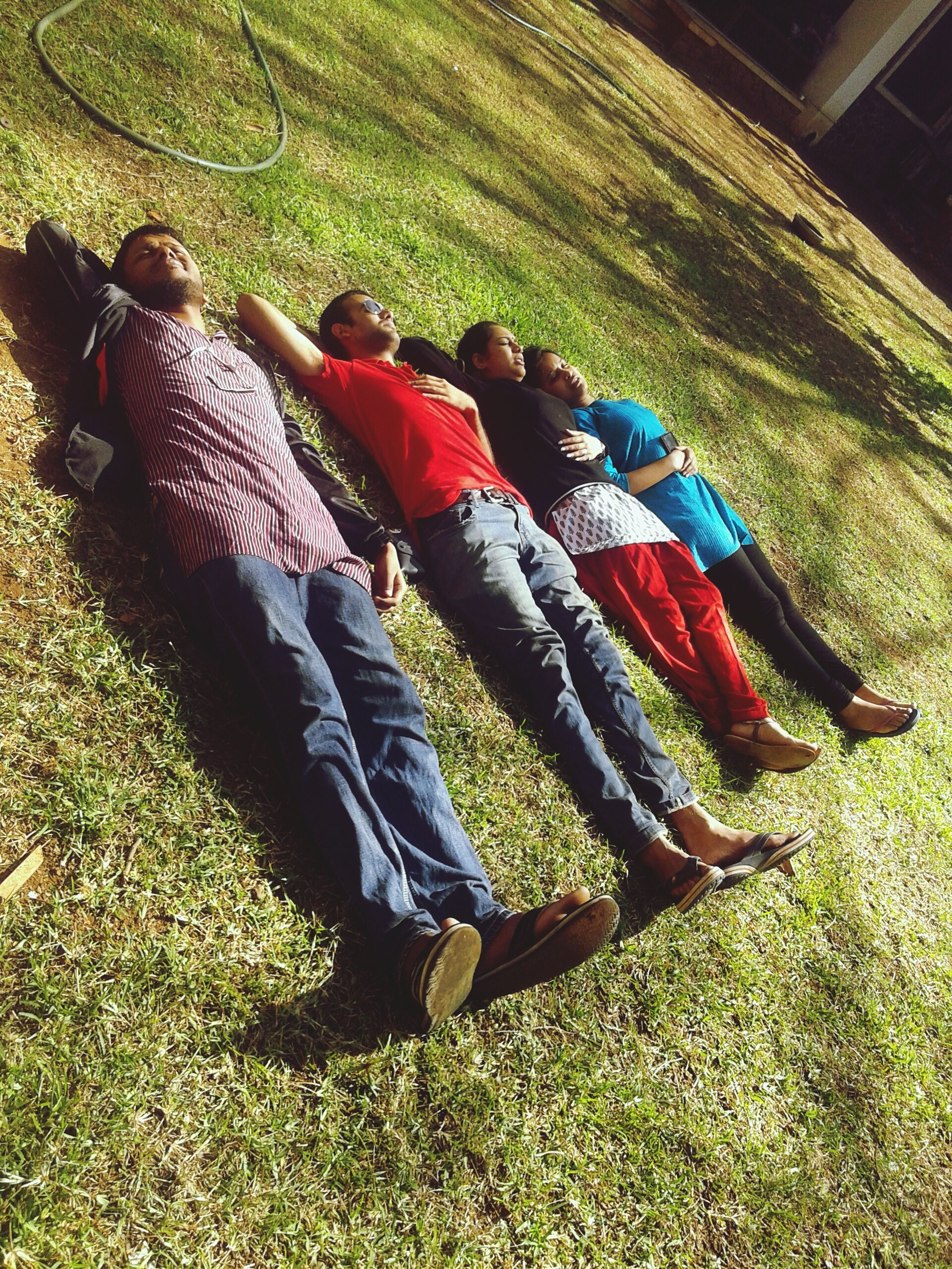 grass, field, grassy, green color, high angle view, men, day, outdoors, shoe, clothing, leisure activity, lifestyles, sunlight, nature, low section, sitting, relaxation, casual clothing