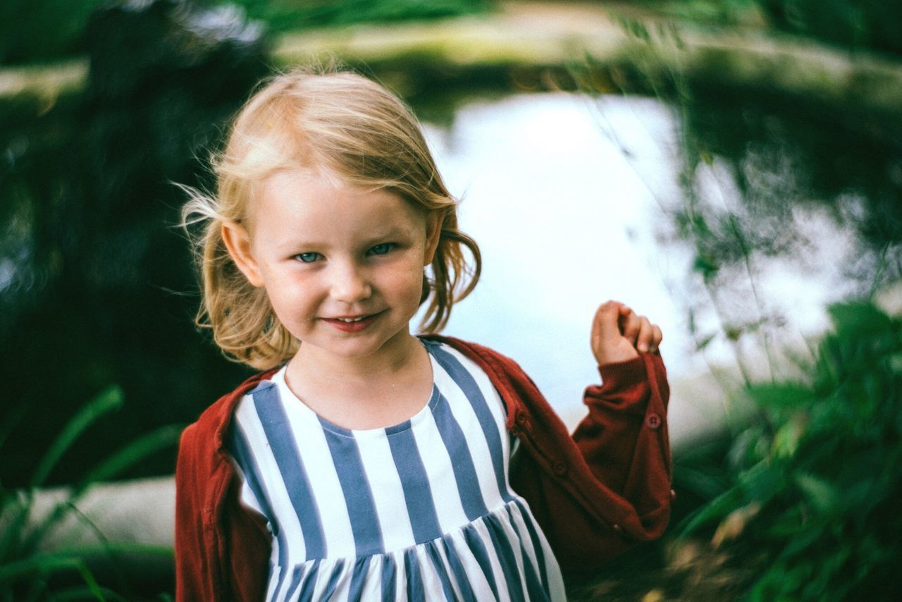 childhood, real people, looking at camera, elementary age, portrait, girls, smiling, cute, one person, striped, happiness, focus on foreground, casual clothing, standing, outdoors, lifestyles, day, blond hair, close-up