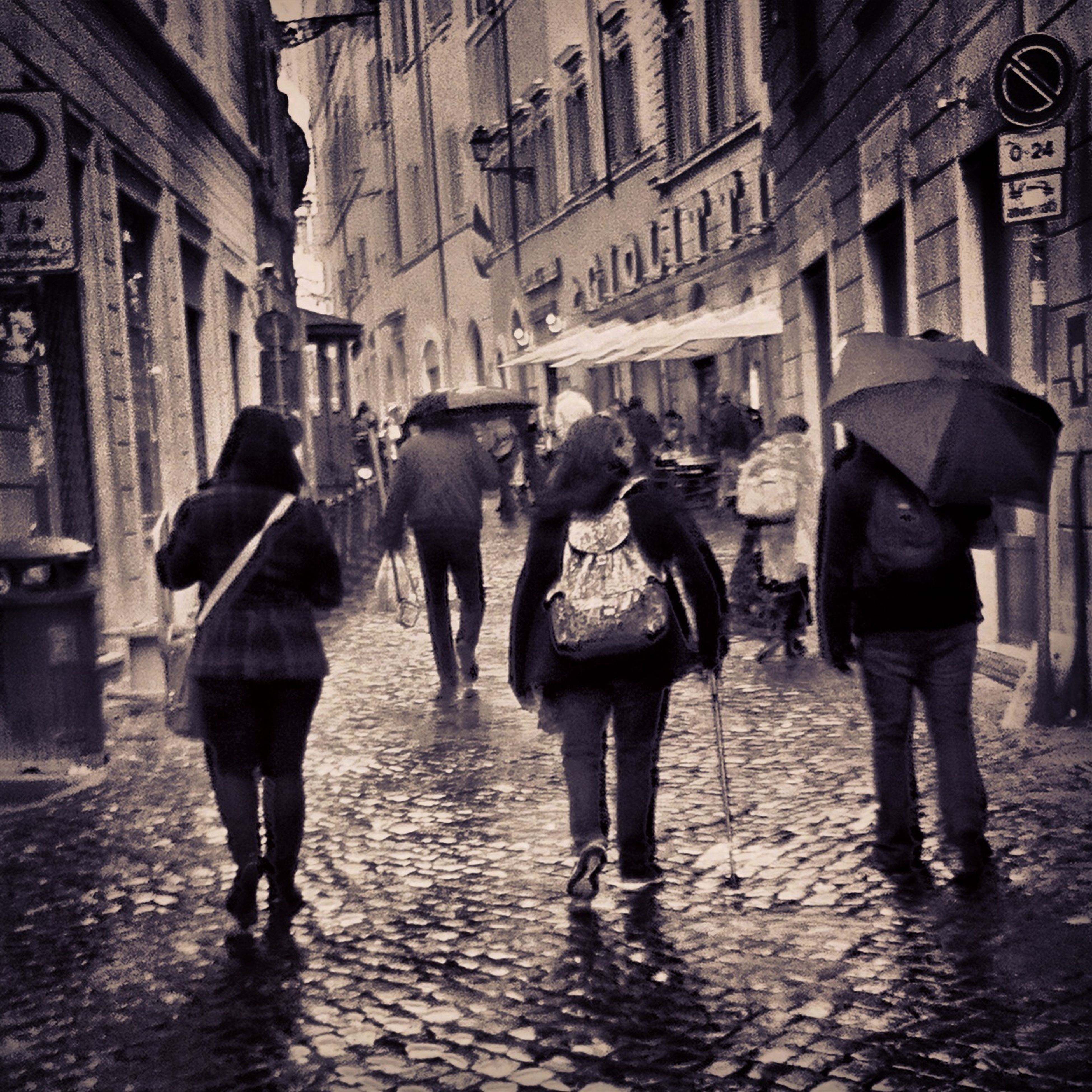 walking, lifestyles, full length, men, rear view, person, street, building exterior, leisure activity, architecture, built structure, city life, umbrella, togetherness, city, casual clothing, standing, rain