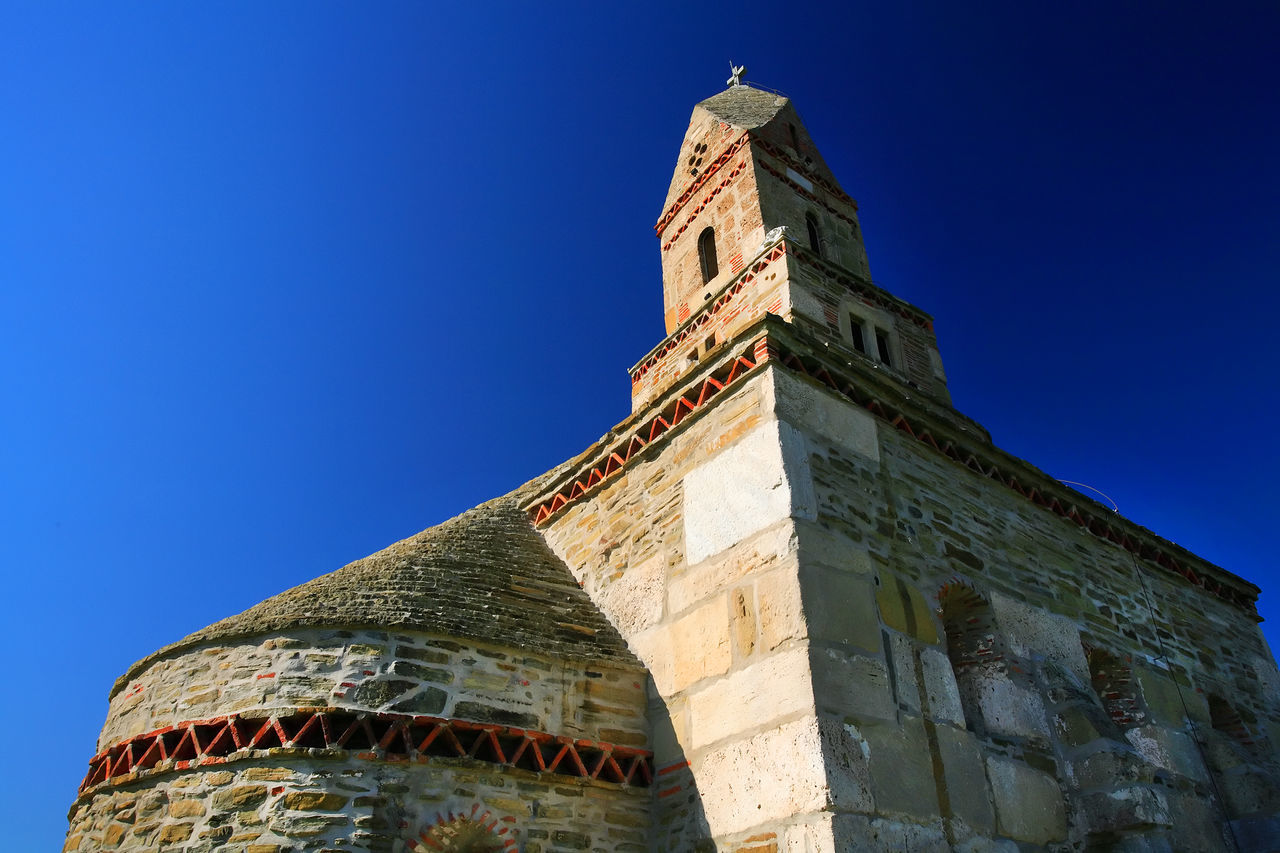architecture, low angle view, building exterior, history, built structure, blue, tower, place of worship, religion, day, travel destinations, spirituality, no people, outdoors, sunlight, clear sky, clock tower, clock, bell tower, sky