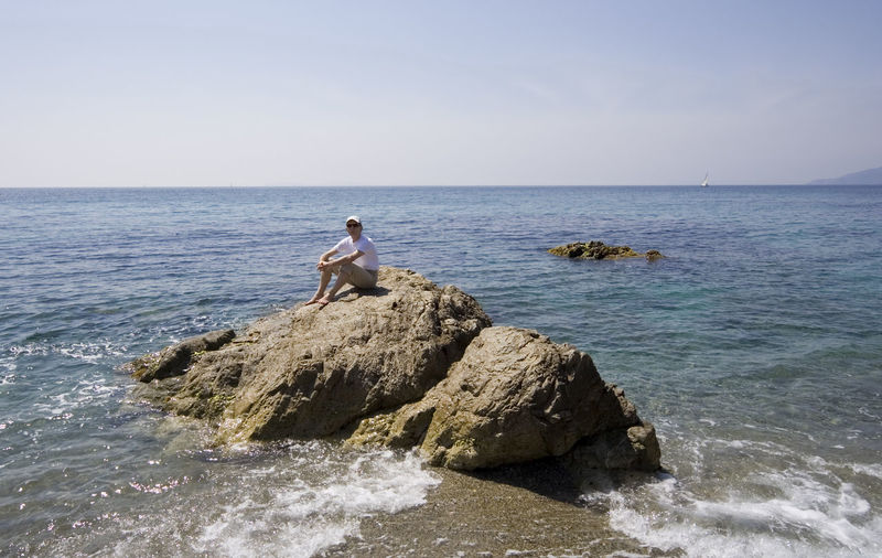 man on the rocks - french riviera, mediterranean sea Barefoot Beach Beauty In Nature Boulder Cliff Côte D'Azur France Full Length Horizon Over Water Lonely Man Mediterranean Sea Nature On Top Of The World One Man Only People Provence Relaxation Rock - Object Scenics Sea Sitting Summer Vacations Water