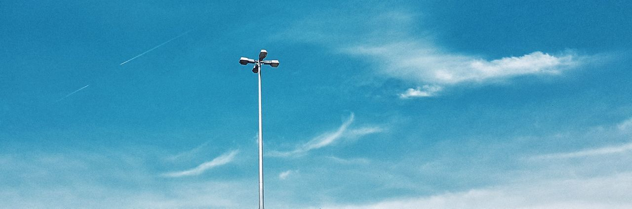 low angle view, sky, day, cloud - sky, blue, outdoors, no people, street light, one animal, nature, contrail, animal themes, bird, vapor trail