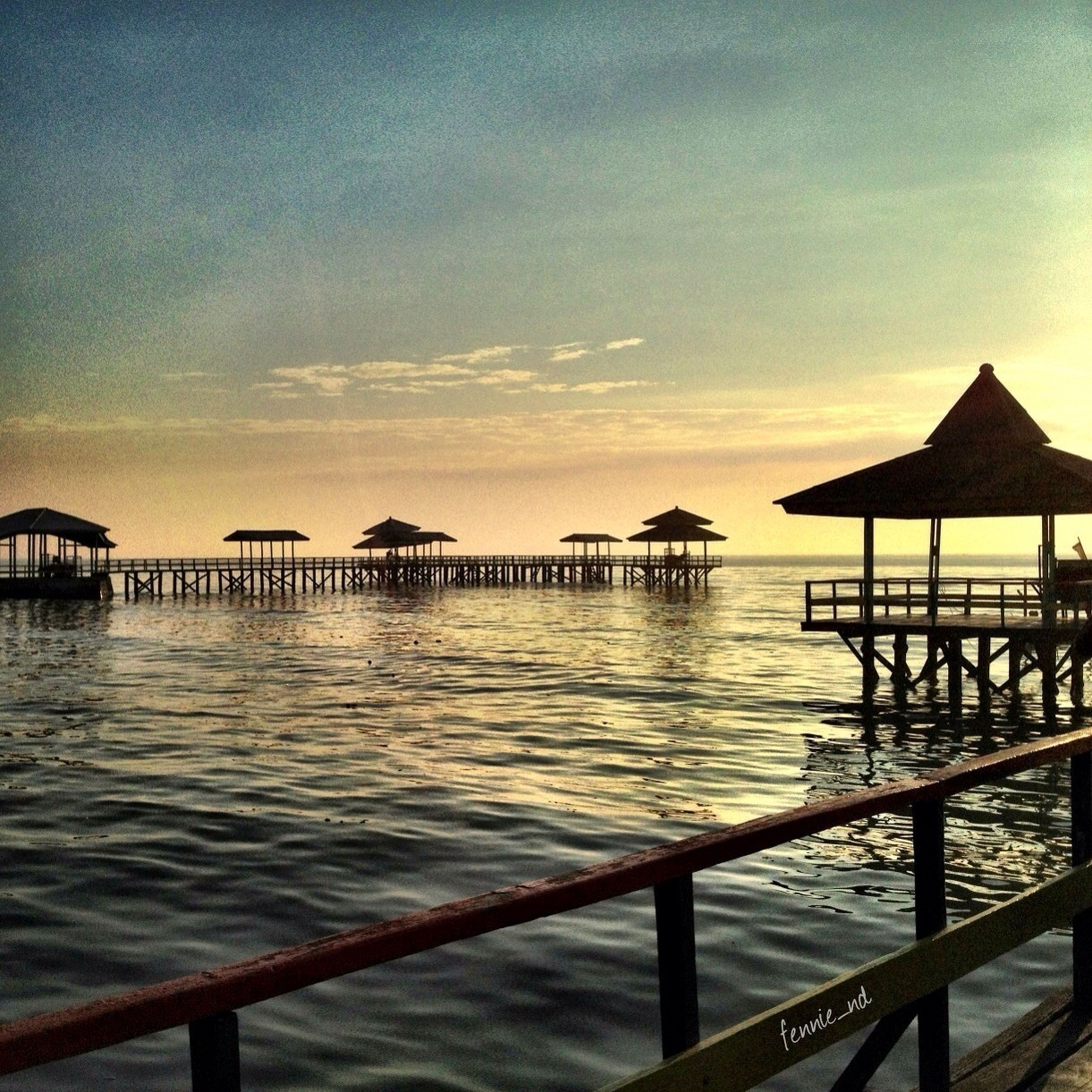 water, sea, pier, sky, tranquil scene, tranquility, scenics, sunset, railing, beauty in nature, jetty, nature, built structure, horizon over water, rippled, wood - material, idyllic, cloud - sky, cloud, ocean