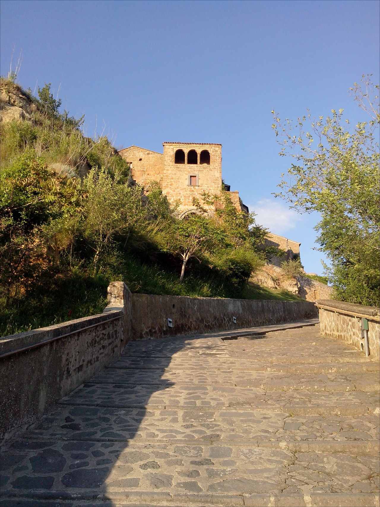 Ancient Architecture Architecture Blue Sky Bridge - Man Made Structure Built Structure Civita Di Bagnoregio Cloudy Sky Footpath Handrails On Top Of A Mountain Pavement Shadows & Lights The City That Is Dying The Past The Way Forward Tuff Tufo Under The Sun Vegetation World Monuments Watch