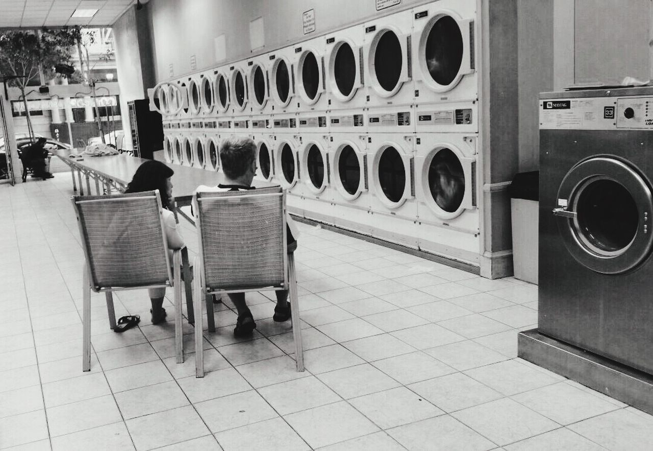 washing machine, laundry, laundromat, dryer, basket, machinery, in a row, table, self service, chair, indoors, relaxation, washing, drying, domestic life, hygiene, no people, day