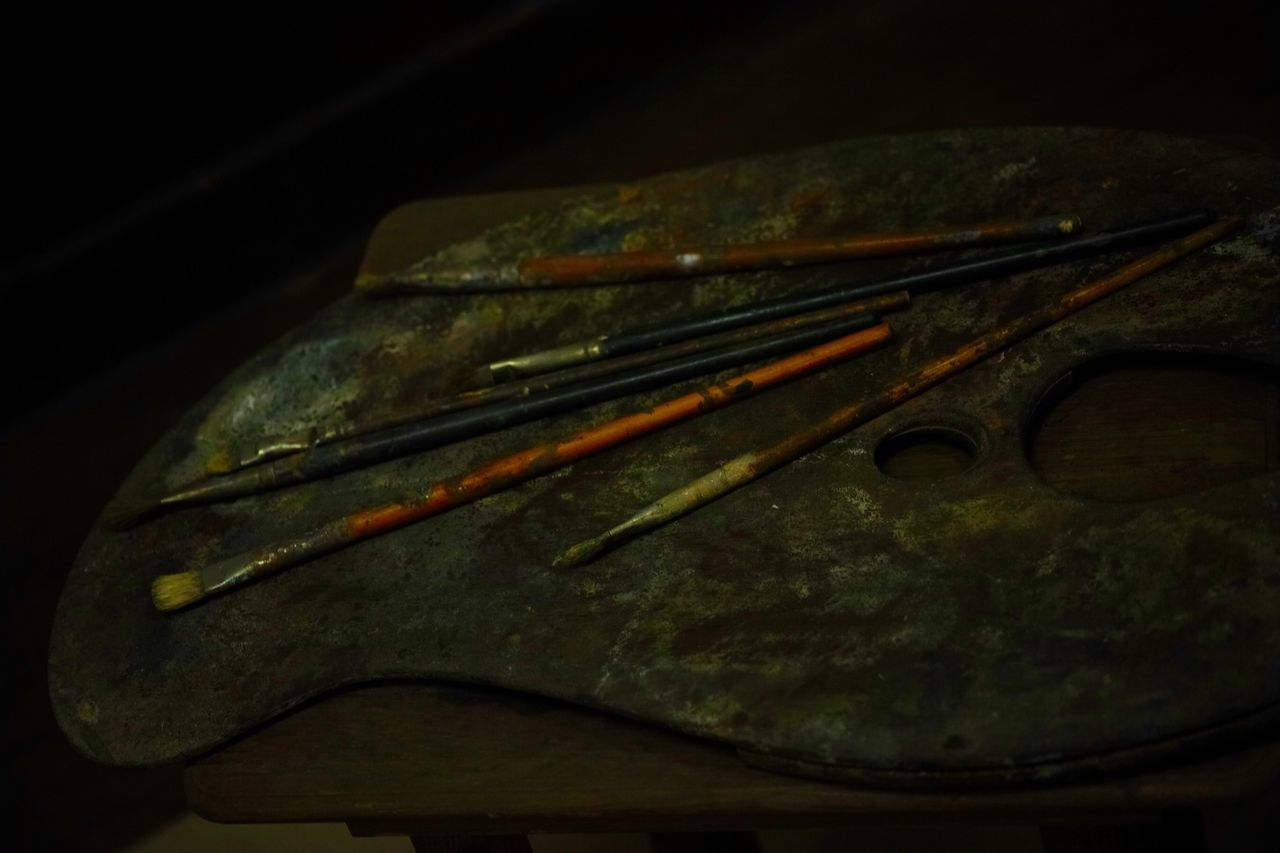 High Angle View Of Old Brushes And Palette On Table
