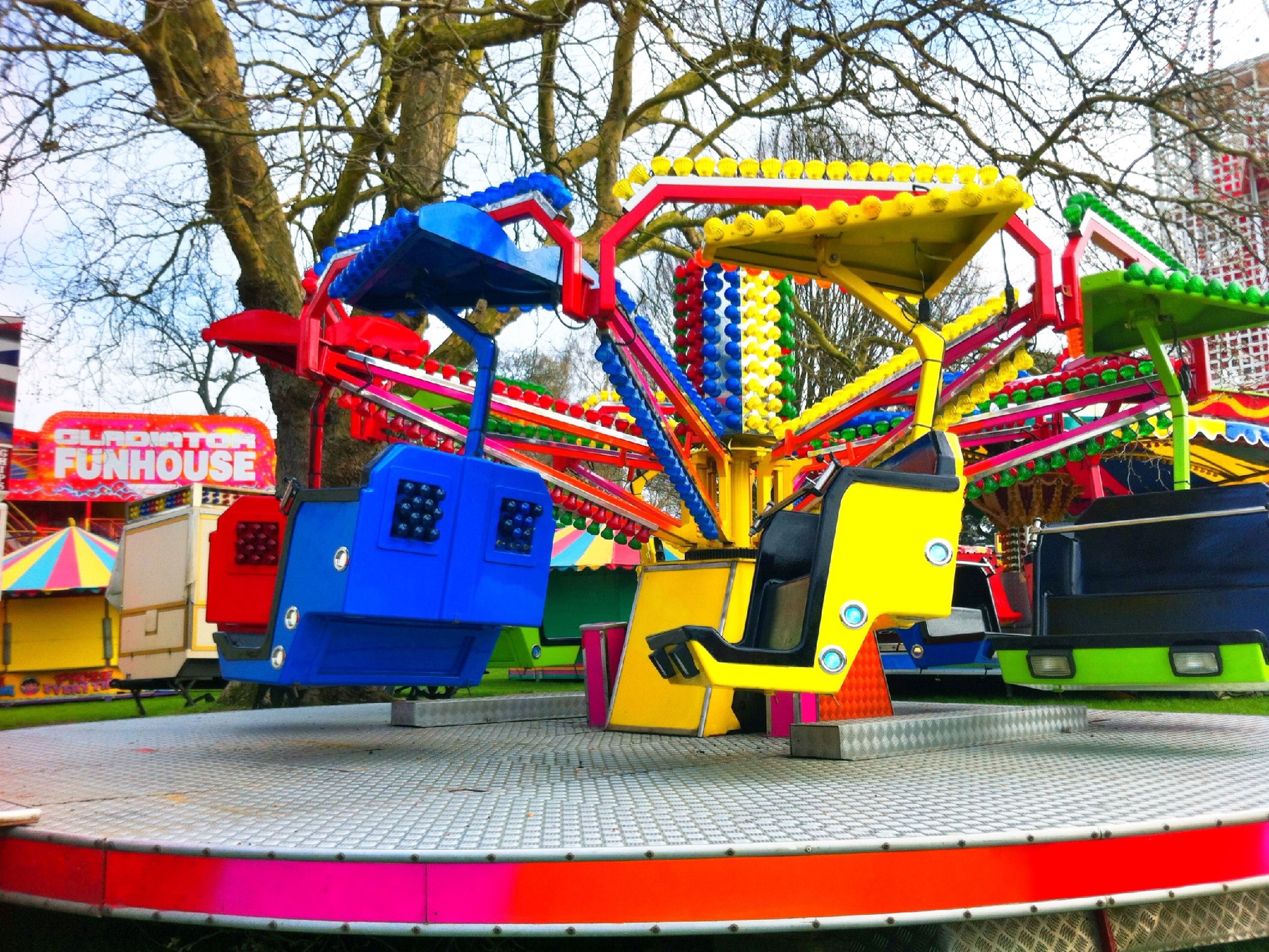 tree, multi colored, built structure, red, transportation, blue, architecture, building exterior, day, metal, land vehicle, outdoors, mode of transport, railing, yellow, no people, sunlight, playground, low angle view, childhood