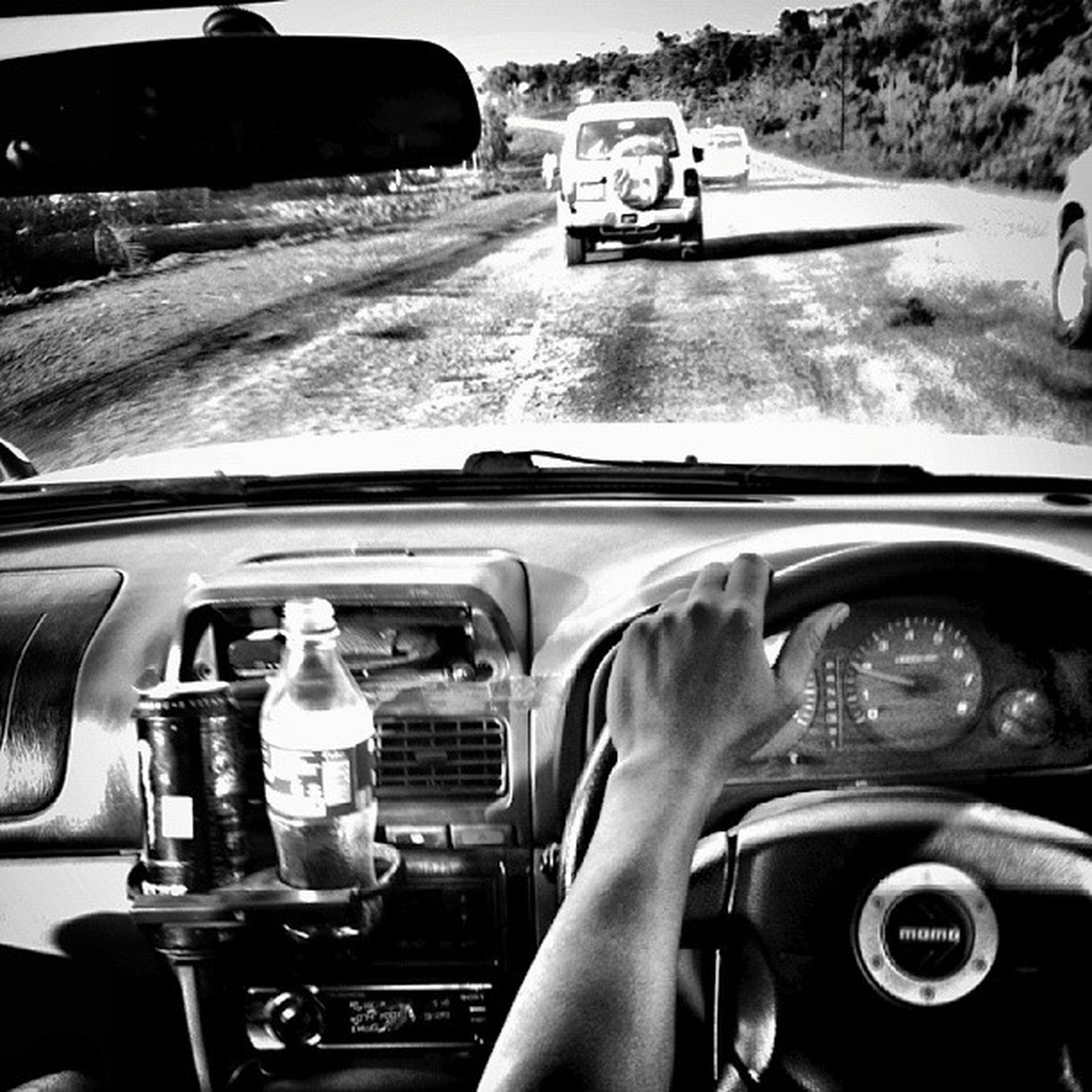 transportation, land vehicle, mode of transport, car, travel, part of, windshield, vehicle interior, car interior, steering wheel, cropped, on the move, side-view mirror, dashboard, vintage car, street, stationary, road, one person, headlight