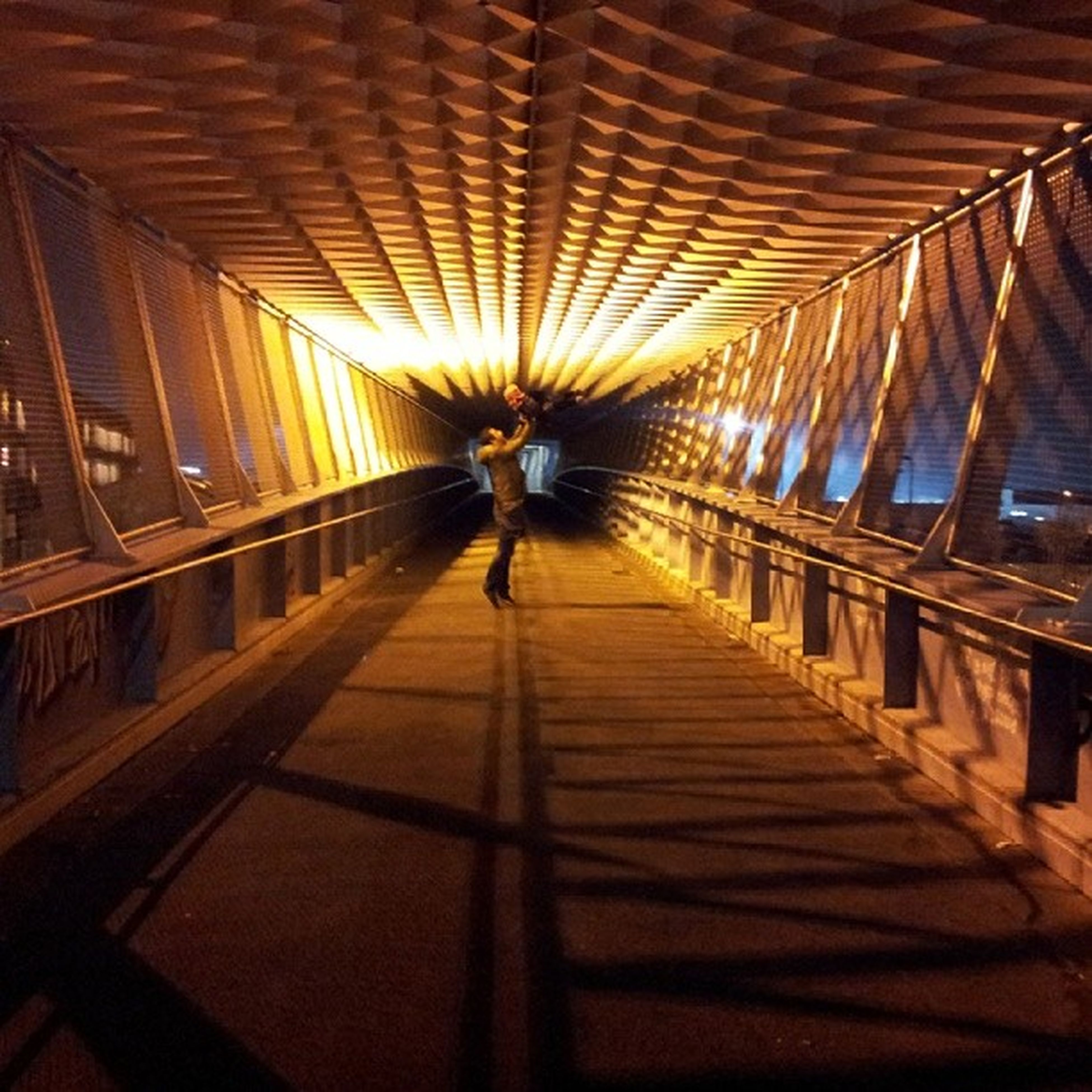 indoors, the way forward, ceiling, architecture, built structure, diminishing perspective, illuminated, lighting equipment, vanishing point, in a row, walking, railing, incidental people, pattern, shadow, transportation, sunlight, full length