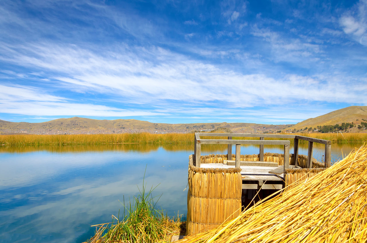Viewpoint on one of the Uros Floating Islands on Lake Titicaca in Peru with Puno visible in the background Altitude Andes Architecture Coutryside Floating High Inca Lake Landmark Landscape Manmade Nature Puno Reed Rural Scenics Sun Titicaca Titicaca Lake Totora Traditional Uros Uros Island Water Waterfront