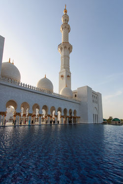 Abu Dhabi, United Arab Emirates - October 10,2014: Sheikh Zayed Grand Mosque at sunset Abu Dhabi Arabic Arch Arched Architecture Blue Building Exterior Built Structure Clear Sky Day Dome Façade Faith History Islam Mosque People Place Of Worship Sheik Zayed Mosque Tall Tower Town Square United Arab Emirates Waterfront White Mosque
