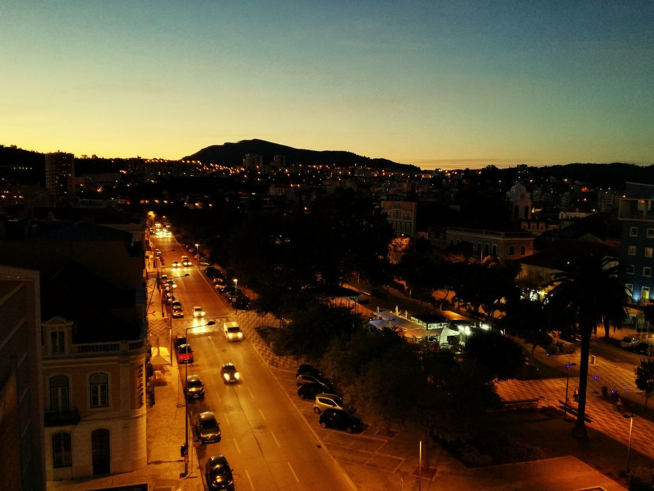 illuminated, transportation, architecture, building exterior, built structure, road, high angle view, outdoors, street light, no people, city, night, sky, clear sky, sunset, tree, cityscape, nature