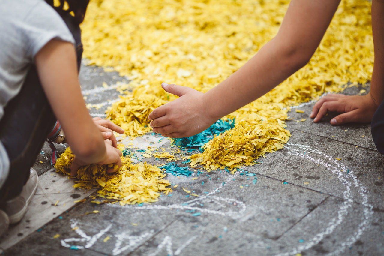 Close-Up Of Children Playing With Confetti