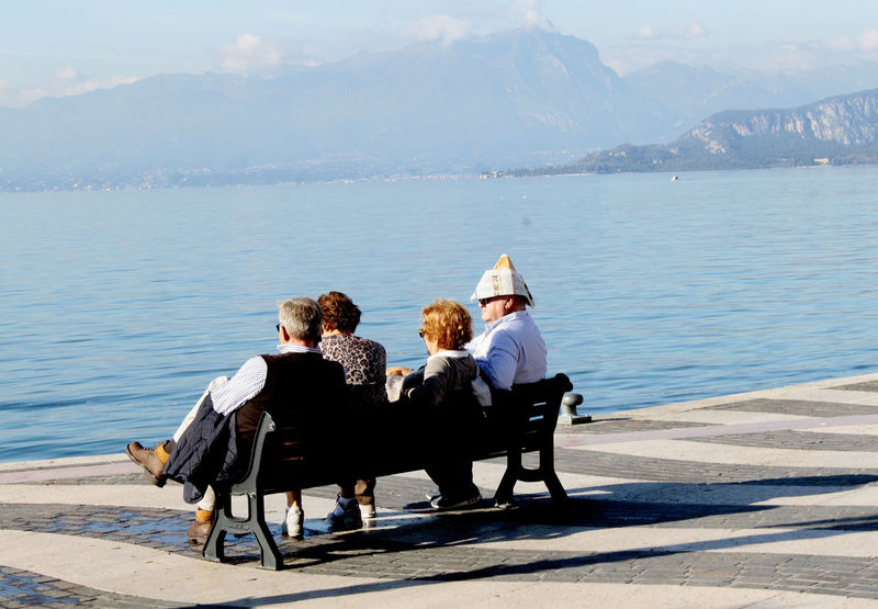 fore guys sitting on a bench, one with a paper hat Autumn Blue Calm Casual Clothing Enjoying Life Freedom Gardasee Happiness Holydays Lago Di Garda Lake Lifestyles Mountain Paper Hat Papierhut People Relaxing Retired Togetherness Tourist Urlaub Vacations Water The Street Photographer - 2017 EyeEm Awards