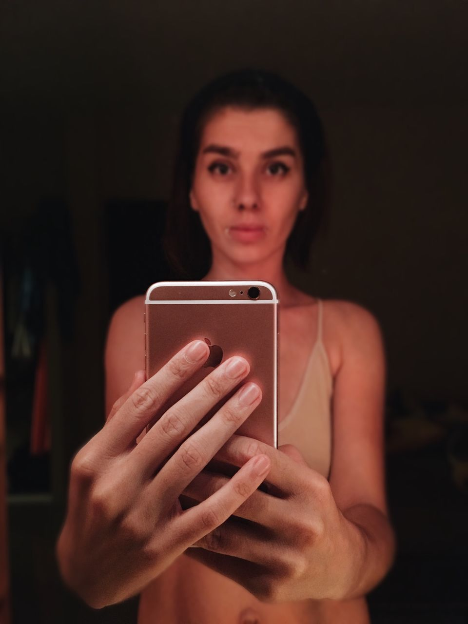 real people, waist up, front view, wireless technology, young adult, holding, one person, focus on foreground, portable information device, leisure activity, indoors, young women, beautiful woman, mobile phone, lifestyles, portrait, standing, looking at camera, studio shot, night, selfie, close-up