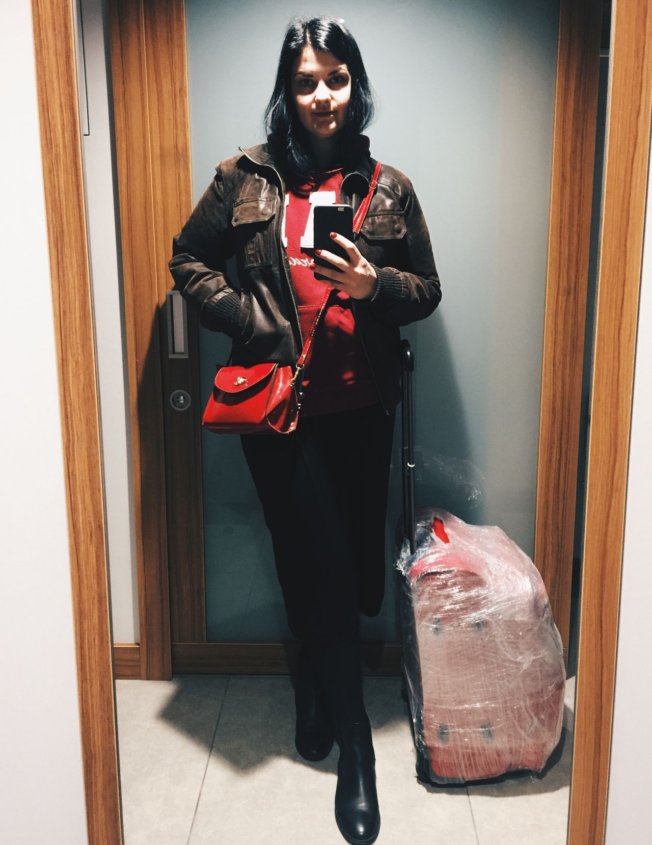 A girl with a lagguage takes a selfie in a hotel room before departing to the airport Bag Baggage Hotel Room Lagguage Leather Jacket Mirror Selfie One Person One Woman Only Only Women Purse Ready To Depart Ready To Leave Selfie Tourist Warm Clothing Wrapped